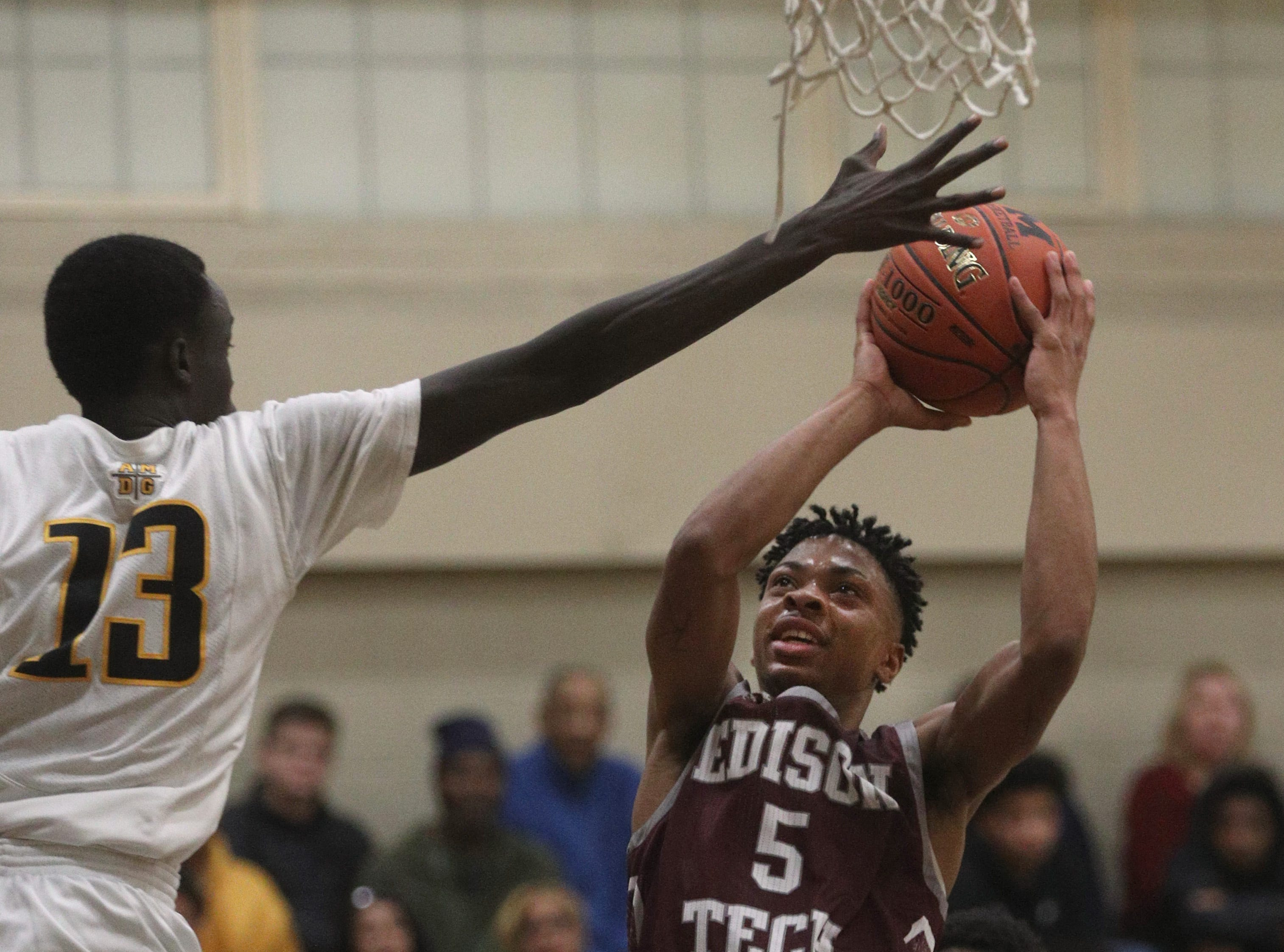 Edison's Alton Knight (5) shoots around the outstretched arm of McQuaid's Rueben Daniel.