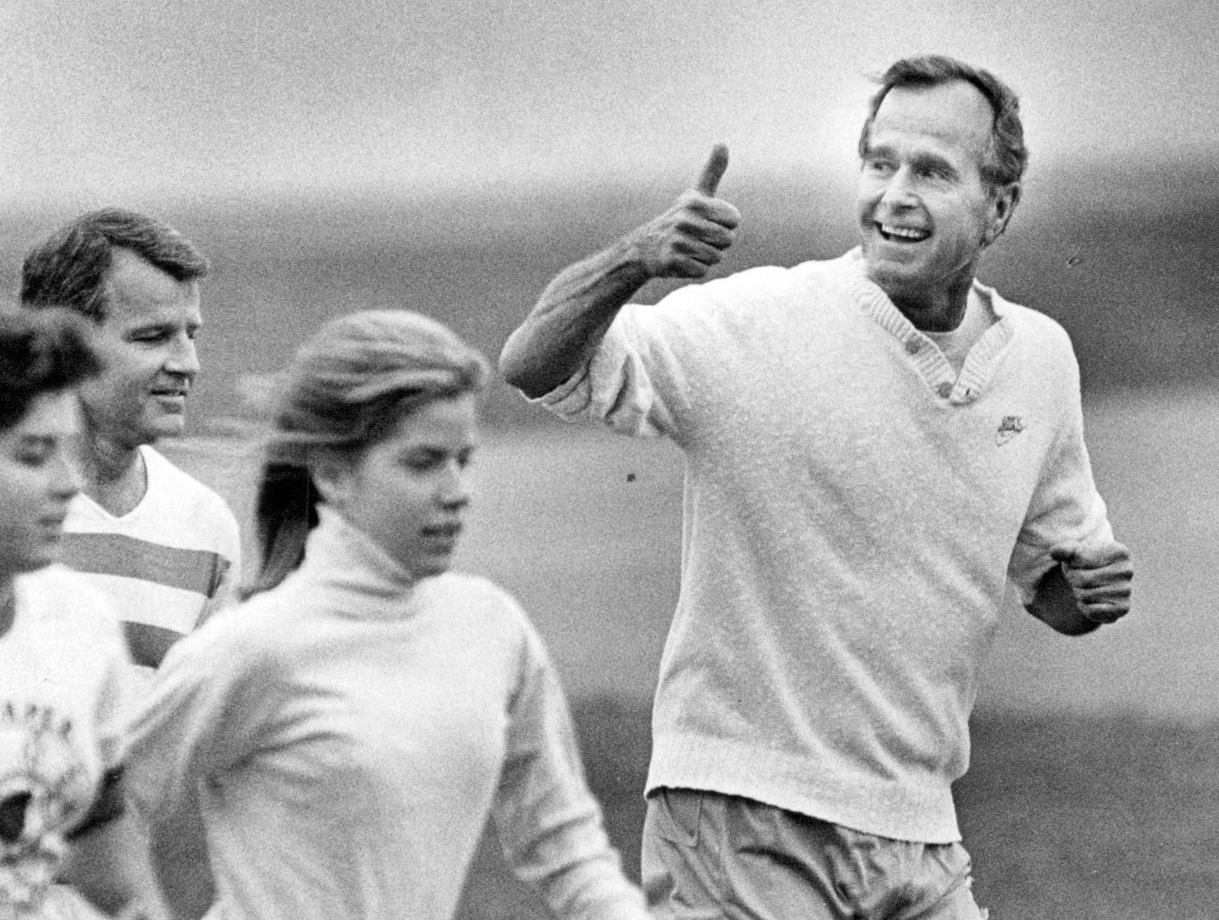 In this photo from 1984, George Bush runs with members of the University of Rochester's women's track team. The 41st President of the United States died late Friday, November 30, 2018.
