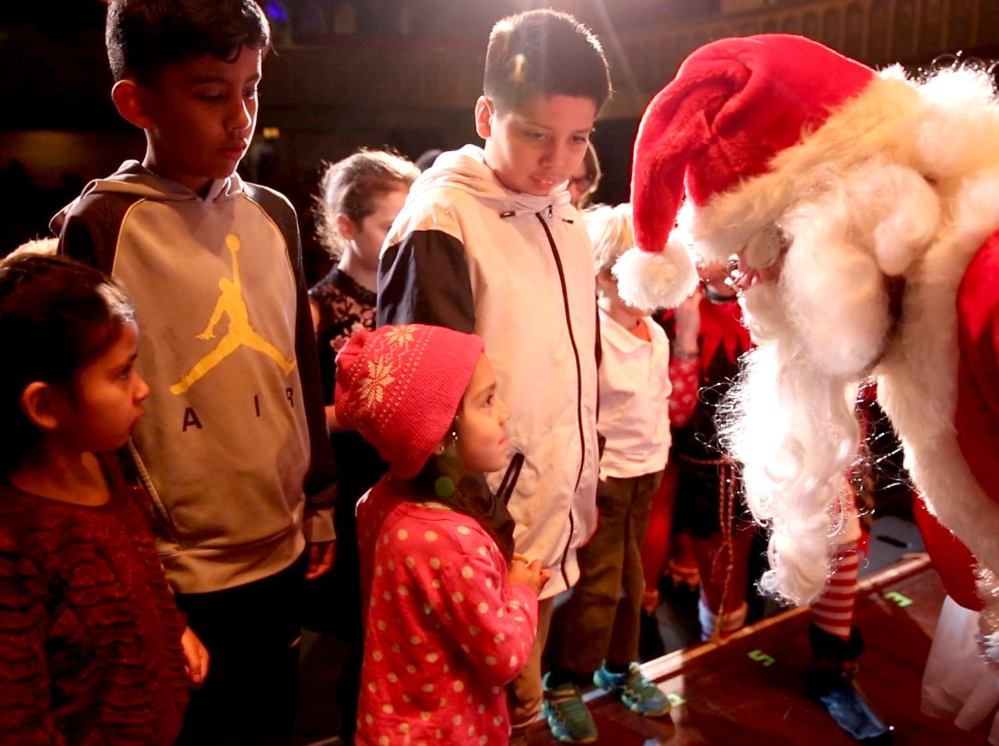 Santa Claus greets siblings Emma Gonzalez and Emiliano Gonzalez at the 78th annual children's holiday party at the Elsinore Theatre on Saturday, Dec. 1, 2018. The party included holiday music and a visit from Santa.