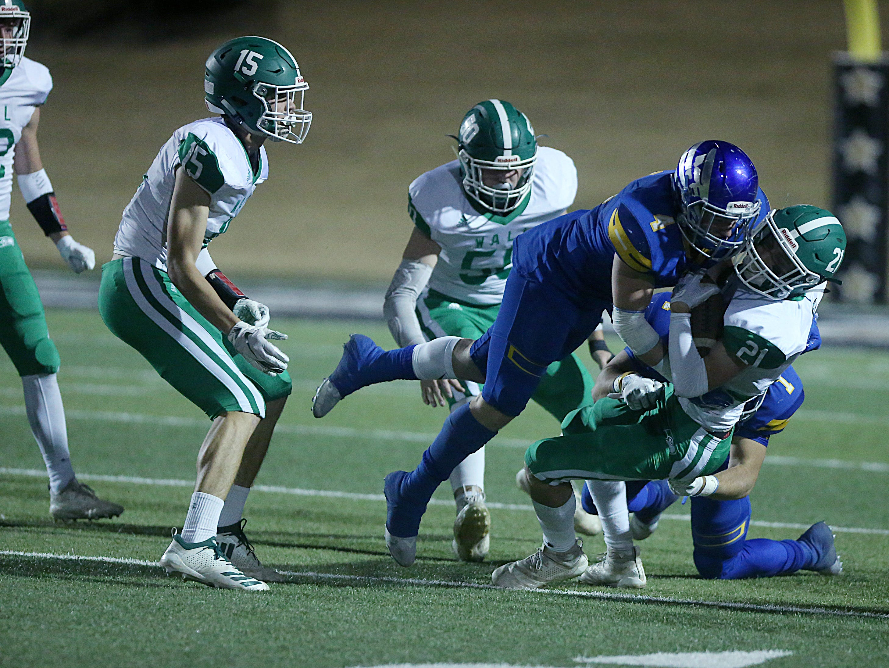 Wall's Lane Ashley (#21) is tackled by Brock's Zakk Young (#4) and Logan Lightfoot (#1) Friday, Nov. 30, 2018, during their game at Shotwell Stadium in Abilene. Wall lost 13 to 35.