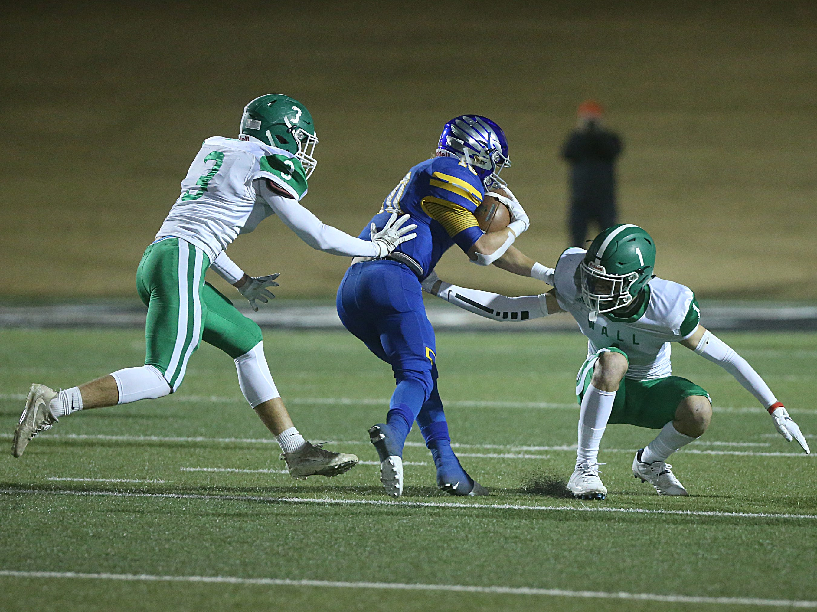 Wall's Joe Walker (#3) and Cameron Barnes (#1) trap Brock's Toby Morrison (#10) Friday, Nov. 30, 2018, during their game at Shotwell Stadium in Abilene. Wall lost 13 to 35.