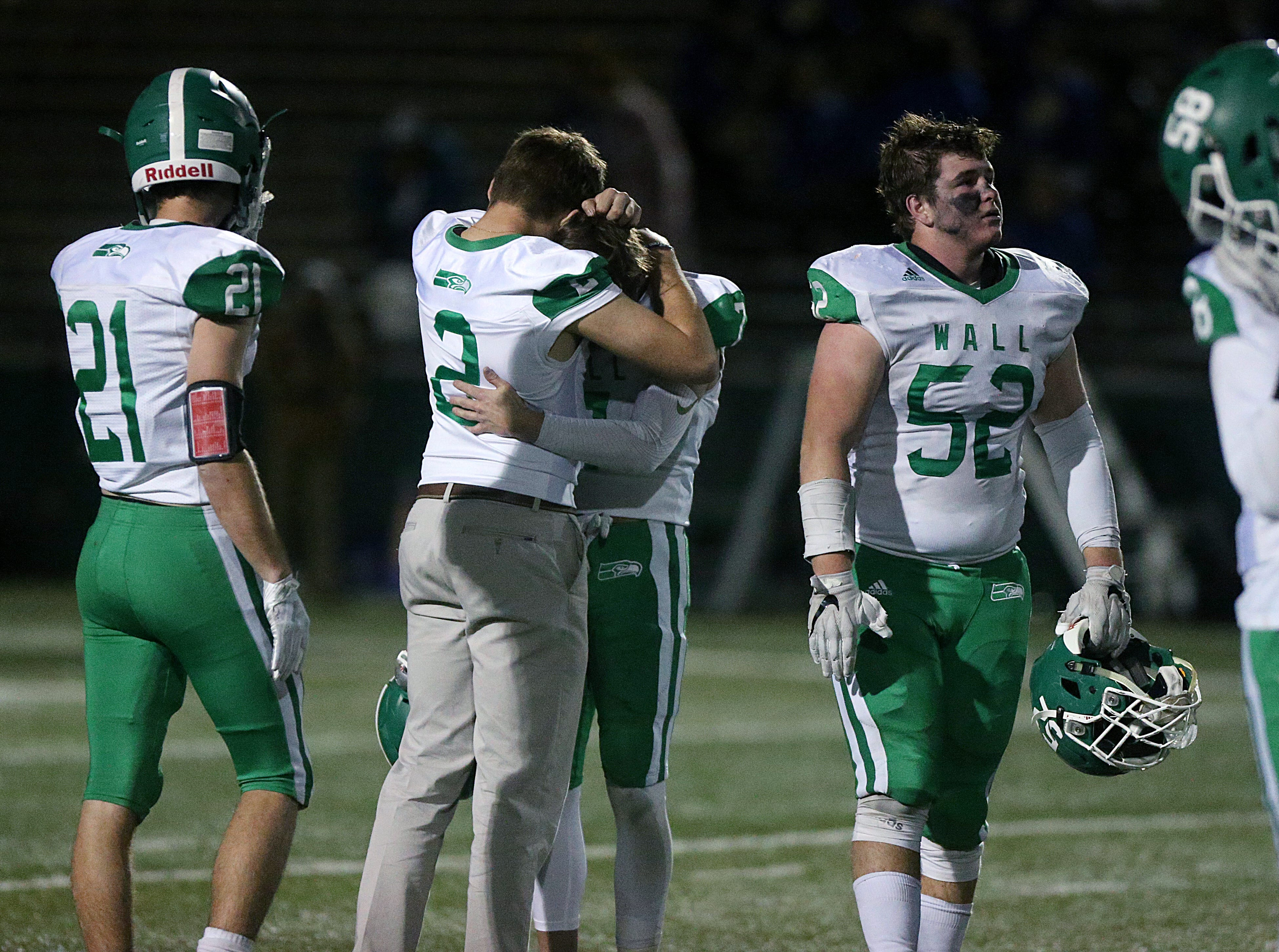 Wall players embrace after their game against the Brock Eagles Friday, Nov. 30, 2018, at Shotwell Stadium in Abilene. Wall lost 13 to 35.