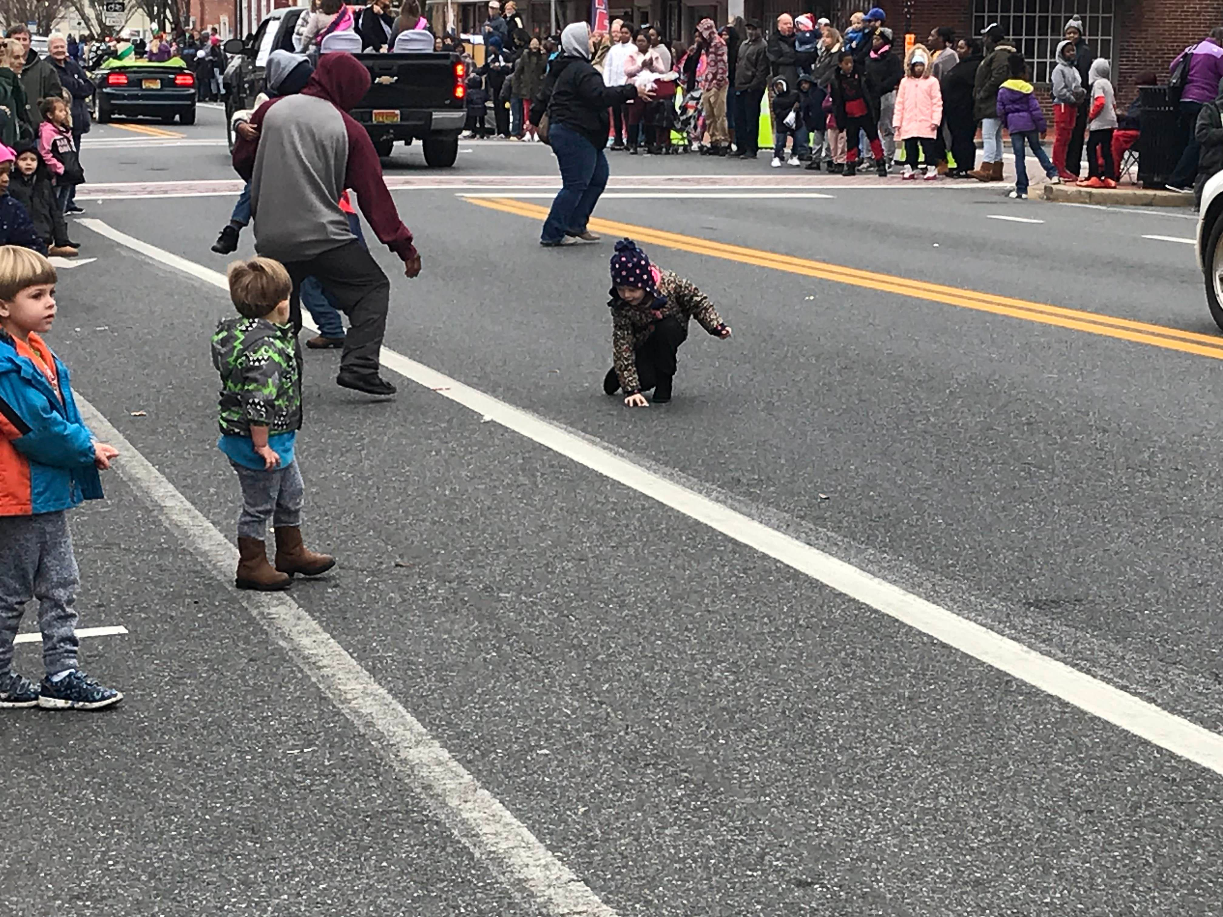 Children collect candy thrown by people in the parade.