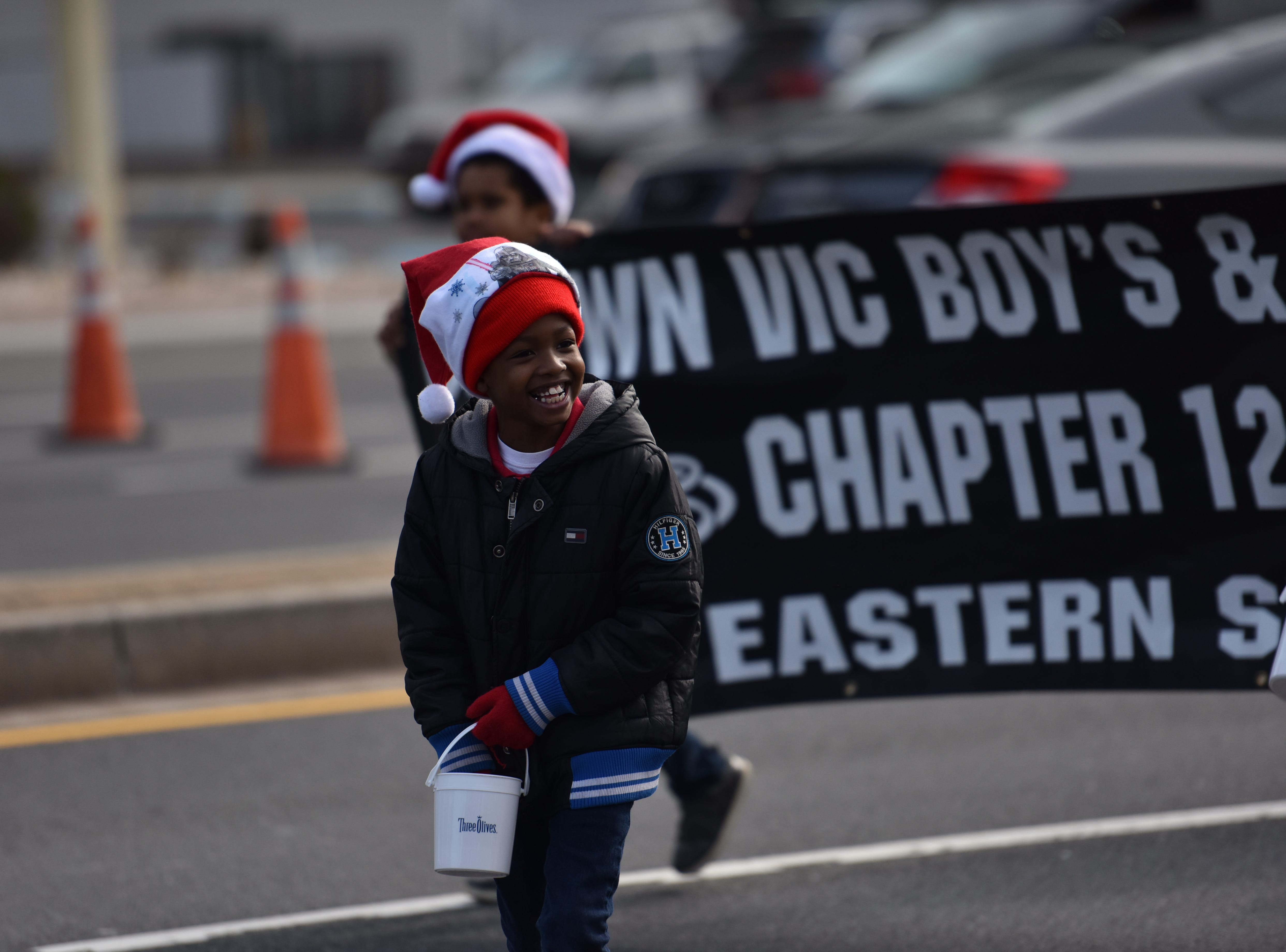 A Boy from Crown Vic Boy's and Girls of Eastern Shore smiling at parade goers at the Ocean City Christmas parade.