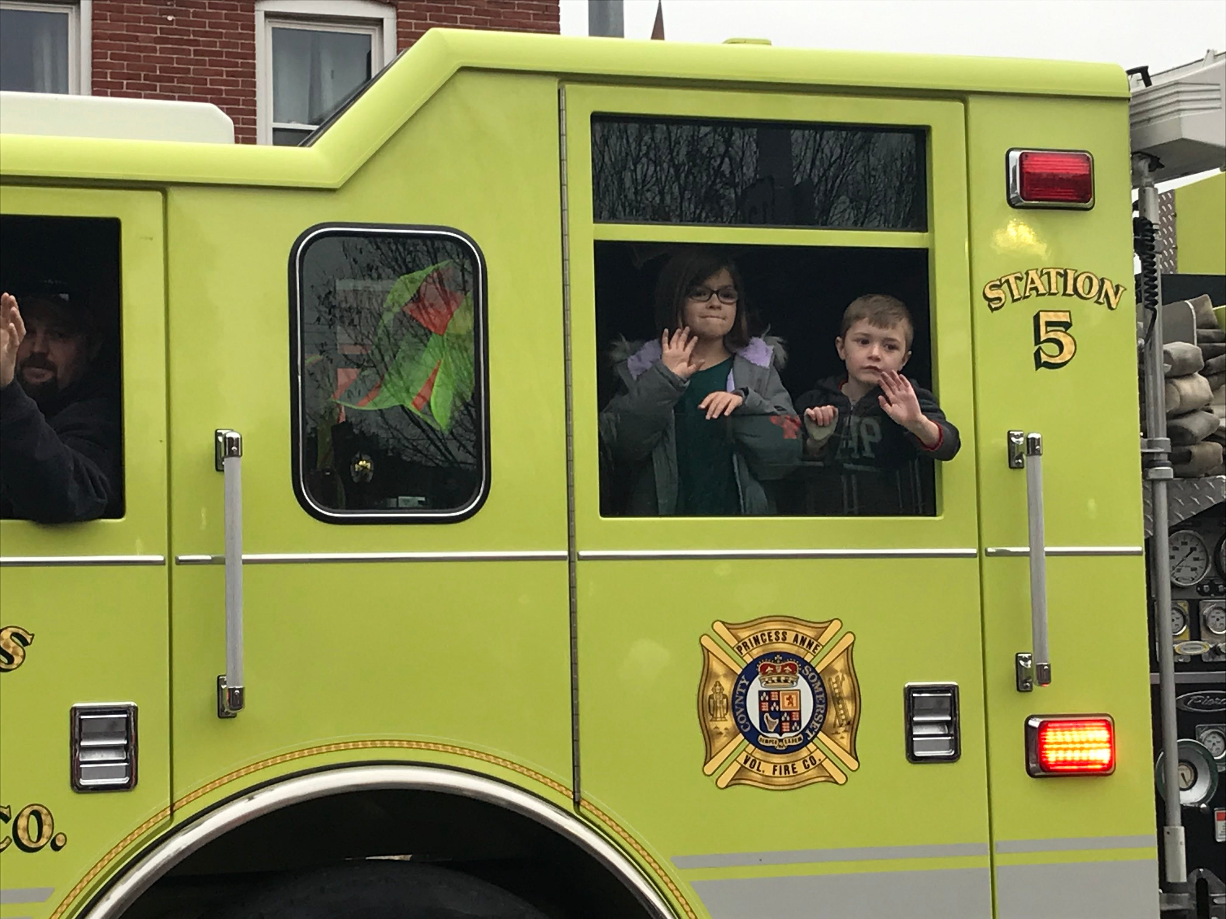 Children in one of the fire trucks wave to people on the street.