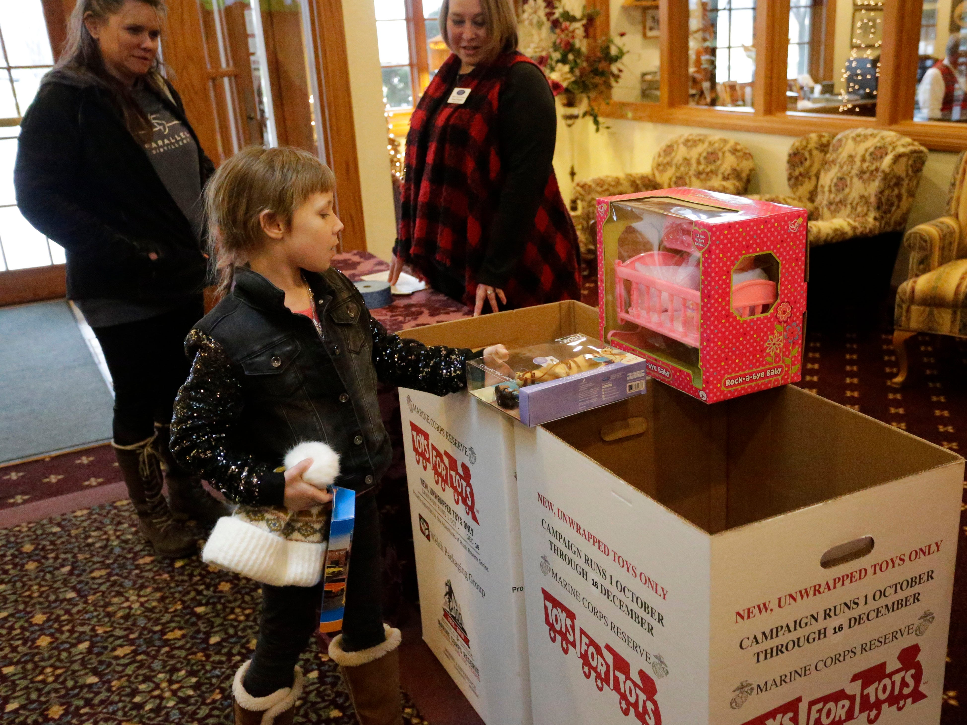 Ella Depies, 7, of Howards Grove, drops off a new toy for Toys for Tots while making a stop for Cookies with Santa at Zimmer Westview Funeral and Cremation Care Center Saturday, December 1, 2018, in Howards Grove, Wis.  The firm also plans to have Santa at Ballhorn Chapels on December 8, 2018.