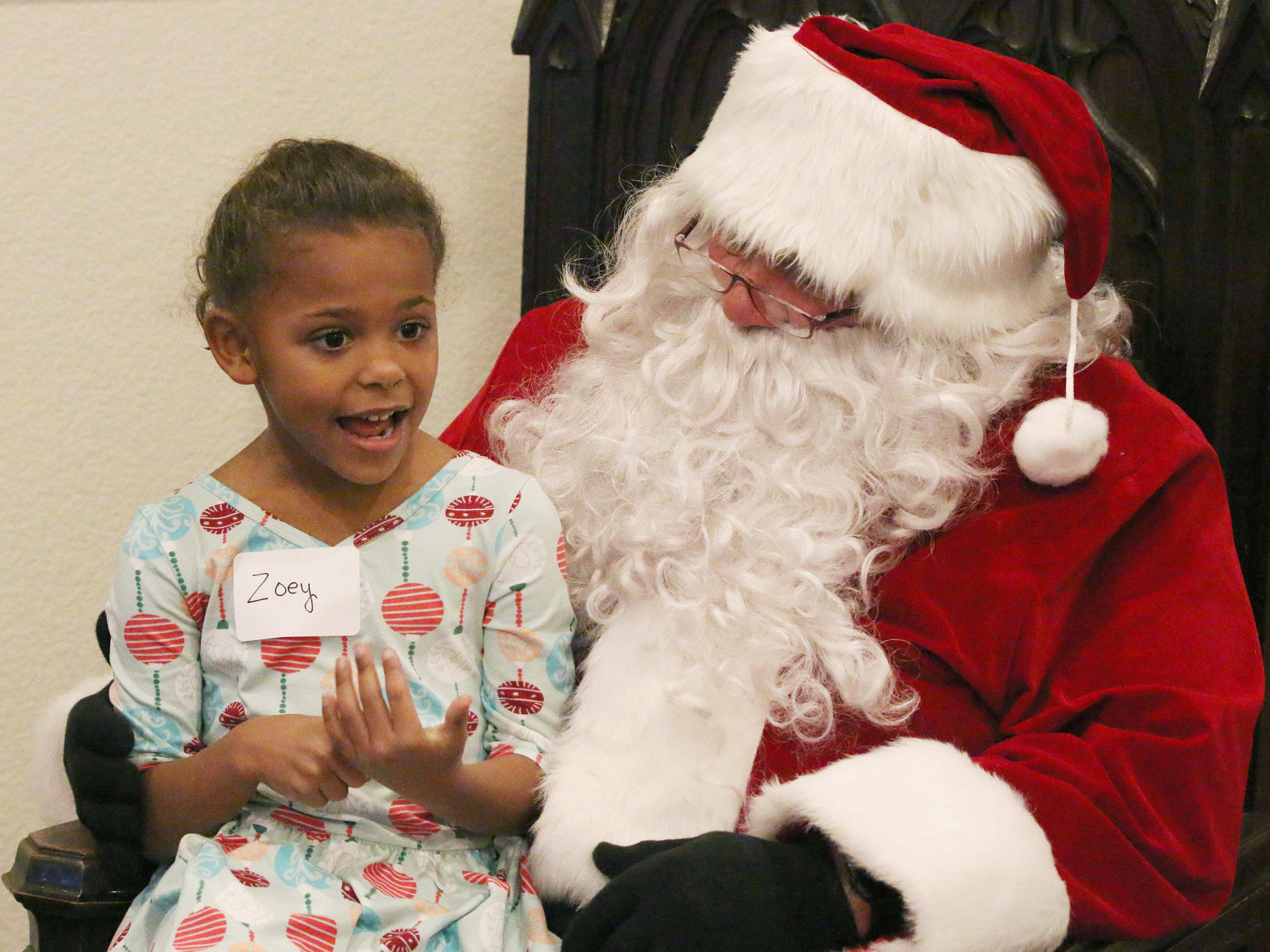 Zoey Arnhoelter, 5, of Sheboygan describes her Christmas list to Santa Claus during Cookies with Santa at Zimmer Westview Funeral and Cremation Care Center Saturday, December 1, 2018, in Howards Grove, Wis.  The firm also plans to have Santa at Ballhorn Chapels on December 8, 2018.
