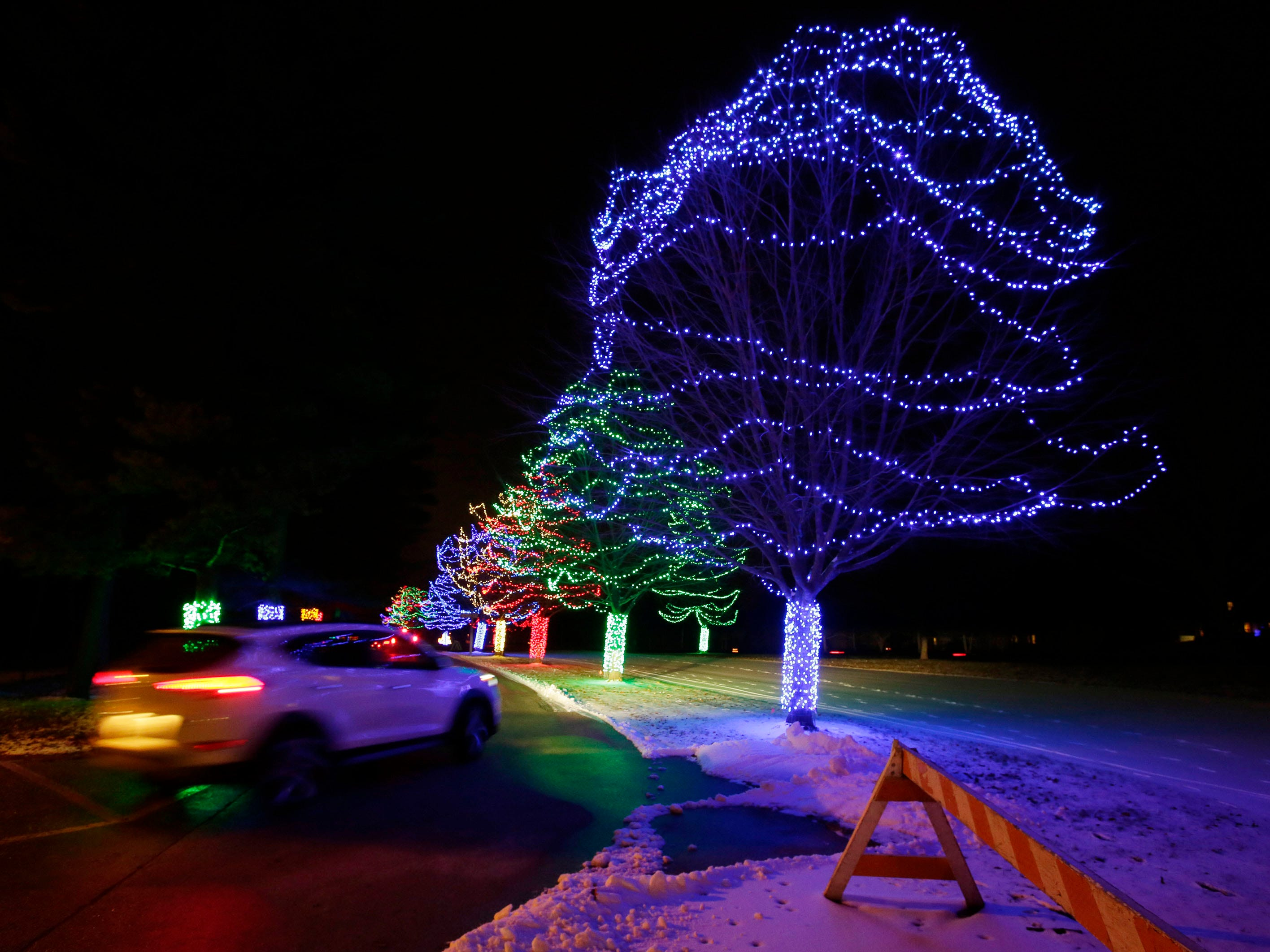 A motorist drives past trees which are brilliant in color at Making Spirits Bright at Evergreen Park, Friday, November 30, 2018, in Sheboygan, Wis.