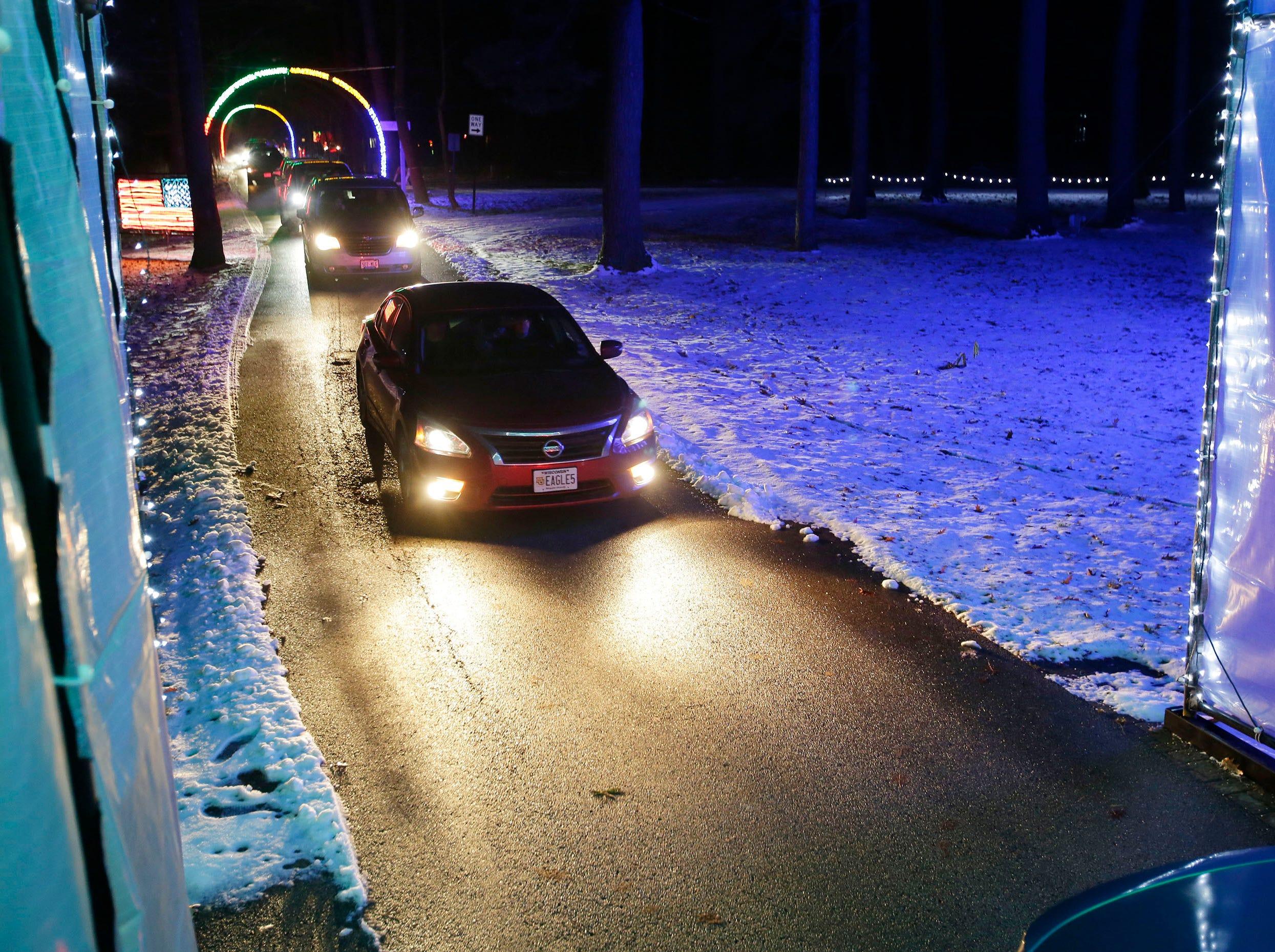 Vehicles enter the igloo at Making Spirits Bright at Evergreen Park, Friday, November 30, 2018, in Sheboygan, Wis.