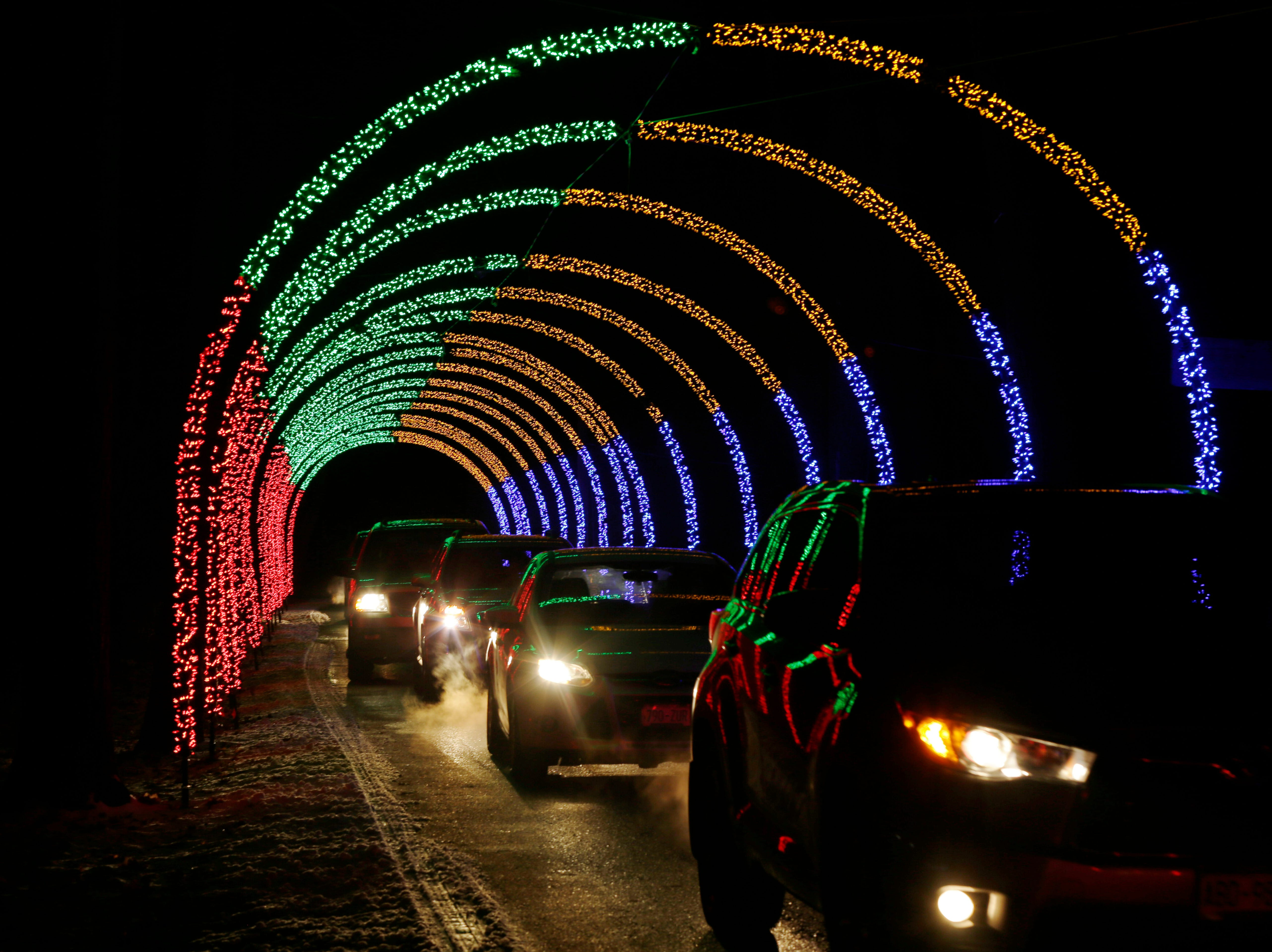 Cars line a tunnel of color at Making Spirits Bright at Evergreen Park, Friday, November 30, 2018, in Sheboygan, Wis.