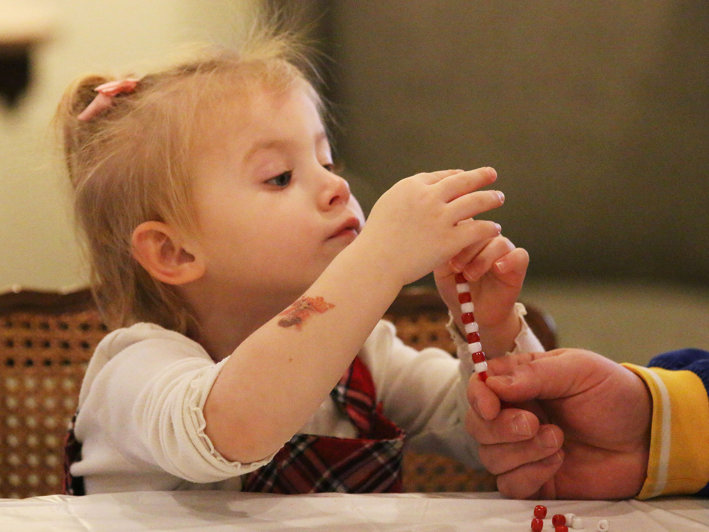 Kadence Baumhardt, 3, of Howards Grove, creates a candy cane bracelet during Cookies with Santa at Zimmer Westview Funeral and Cremation Care Center Saturday, December 1, 2018, in Howards Grove, Wis.  The firm also plans to have Santa at Ballhorn Chapels on December 8, 2018.