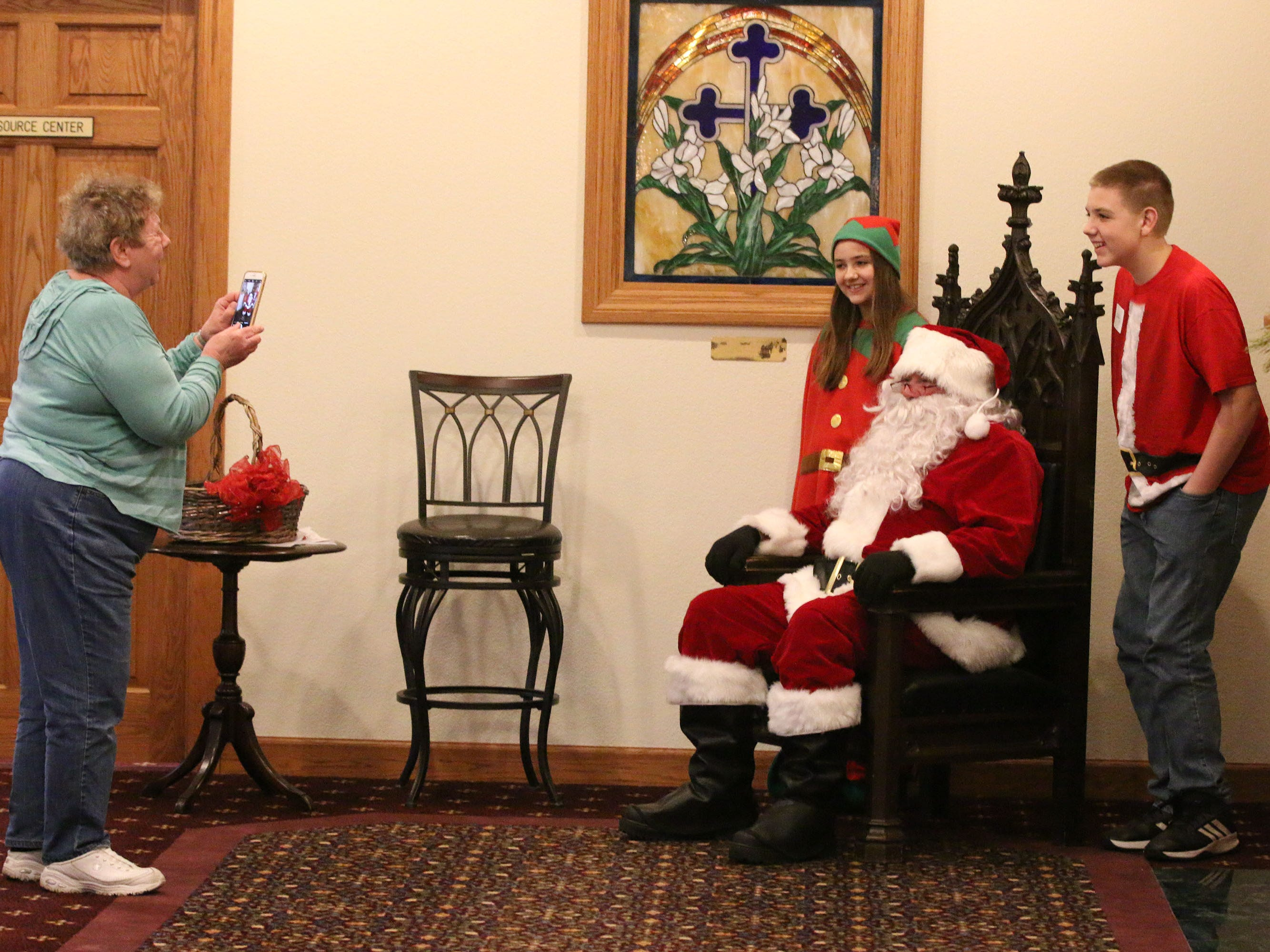 Carol Beyer of Sheboygan, left, snaps a photo of Victoria Perl 11, and her brother Bobby, 13, with Santa during Cookies with Santa at Zimmer Westview Funeral and Cremation Care Center Saturday, December 1, 2018, in Howards Grove, Wis.  The firm plans to have Santa at Ballhorn Chapels on December 8, 2018.