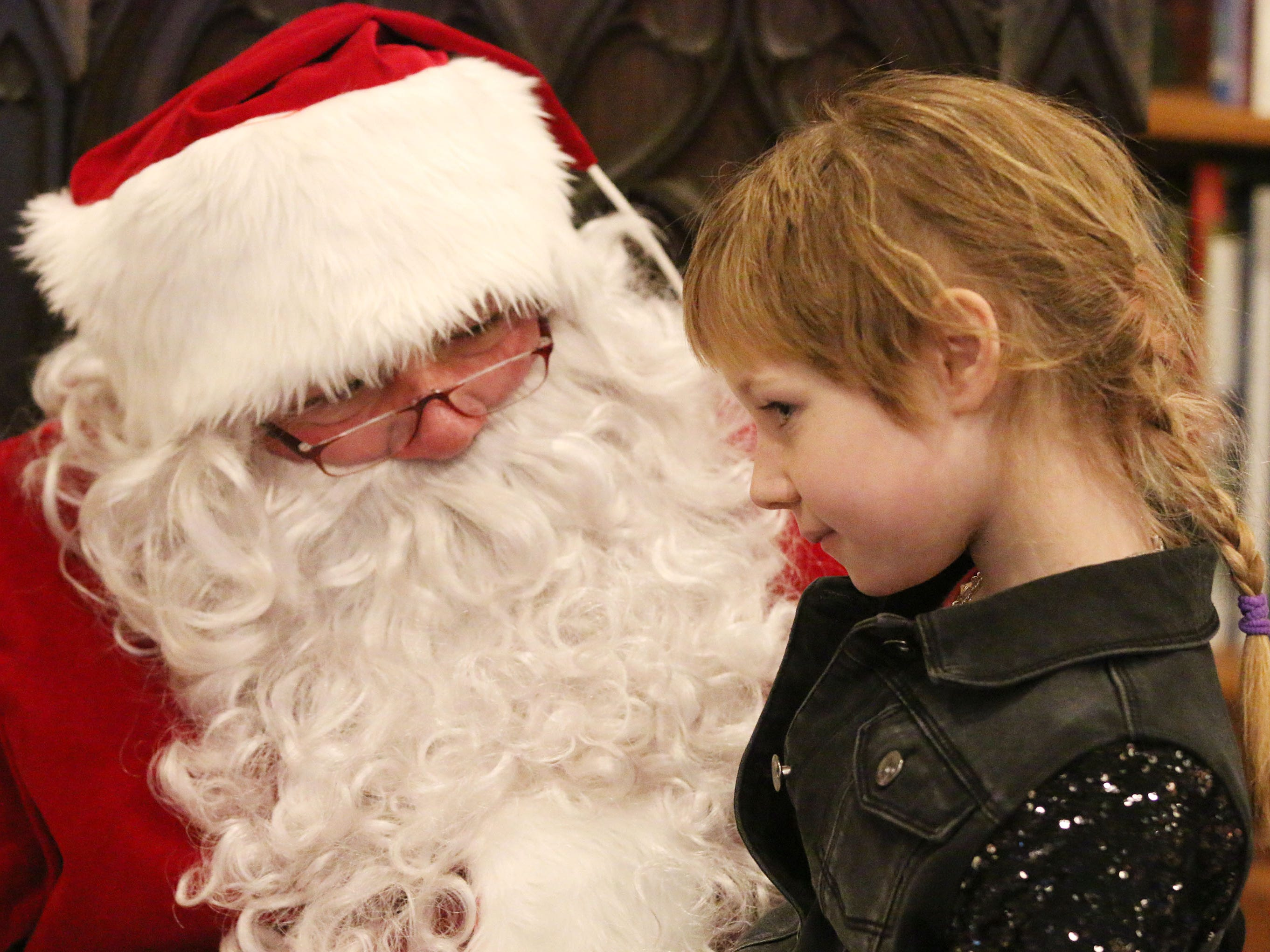Ella Depies, 7, of Howards Grove thinks about her Christmas list while listening to Santa during Cookies with Santa at Zimmer Westview Funeral and Cremation Care Center Saturday, December 1, 2018, in Howards Grove, Wis.  The firm plans to have Santa at Ballhorn Chapels on December 8, 2018.