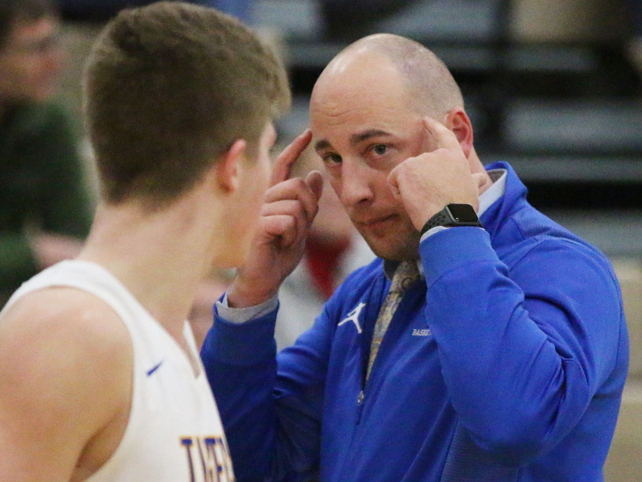 Howards Grove coach Wade Georgeff, right, gives advice to Jack Baldwin (25) during a time out, Friday, November 30, 2018, in Howards Grove, Wis.