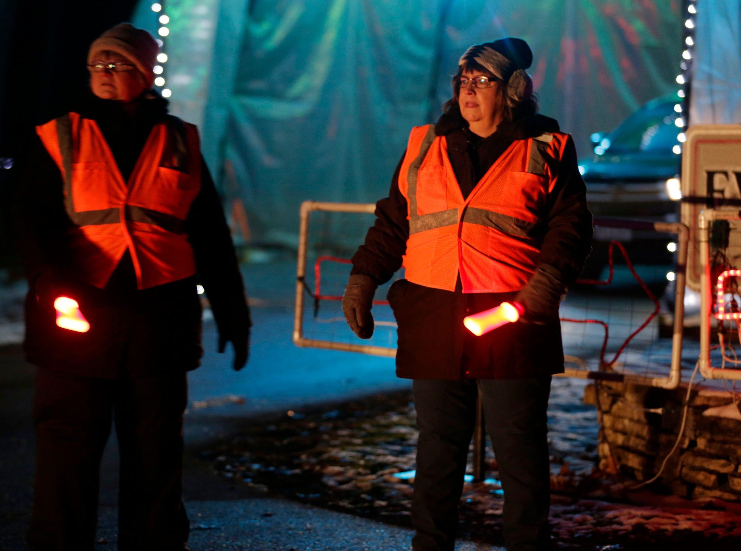 Luann Jenty, left, and Kathy Donlon, both of Sheboygan, help guide motorists at Making Spirits Bright at Evergreen Park, Friday, November 30, 2018, in Sheboygan, Wis.