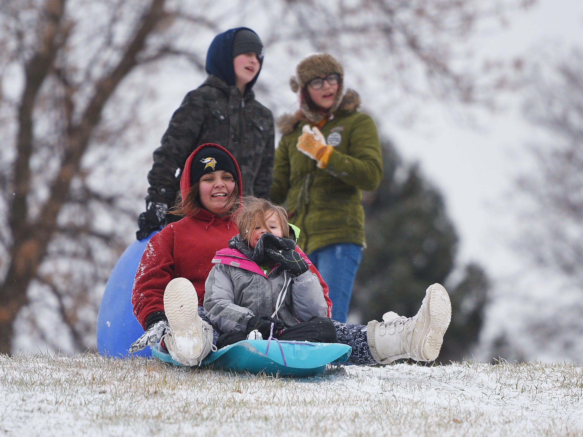 Brittaney Schultz, rear, and Jozie Taylor, front, prepare to sled down the hill near the Midco Aquatic Center Saturday, Dec. 1, in Sioux Falls. Ava Taylor and Santina Buckles, pictured in the back, were sledding with Brittaney and Jozie.