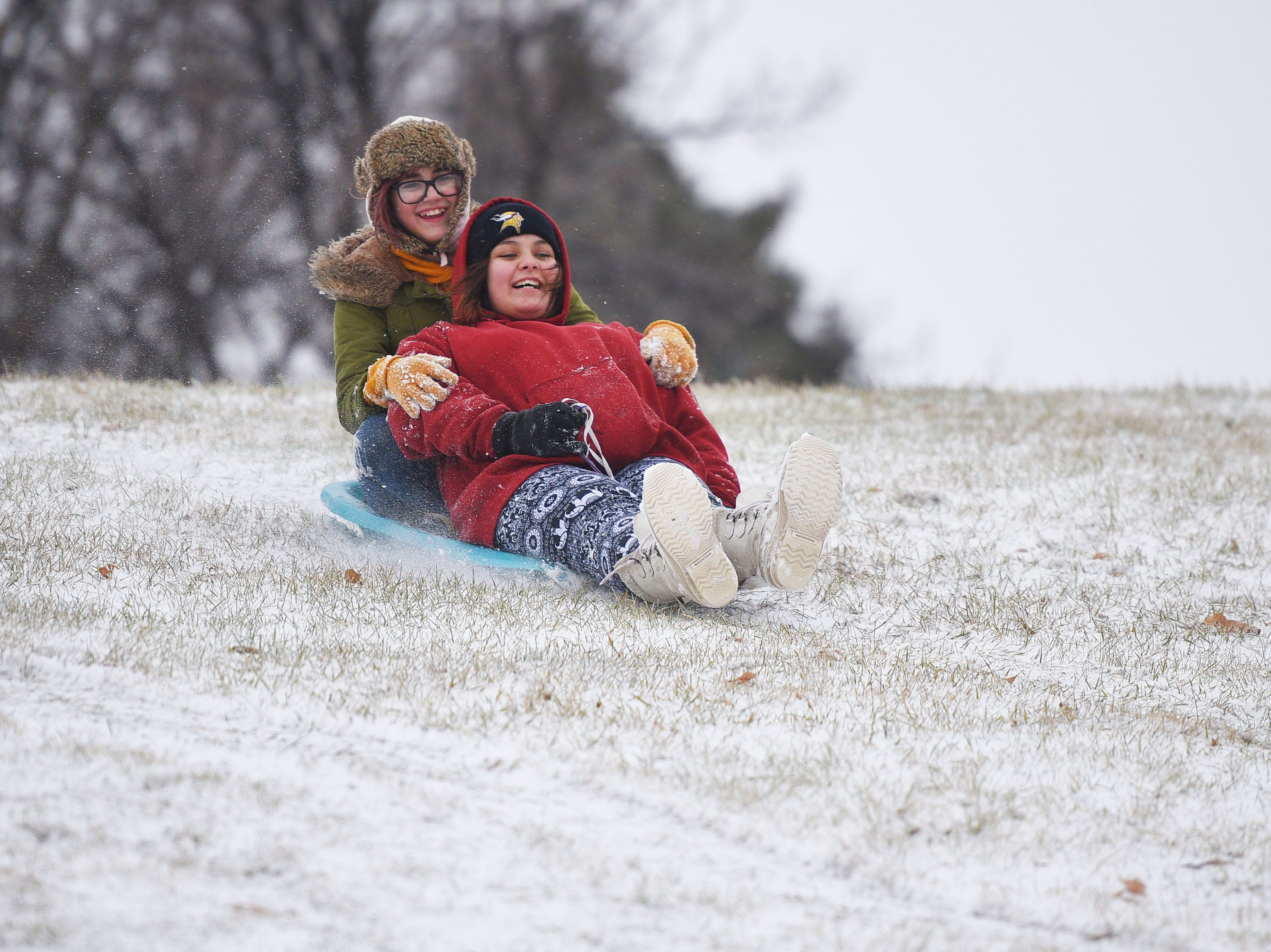 Santina Buckles and Brittaney Schultz sled down the hill near the Midco Aquatic Center Saturday, Dec. 1, in Sioux Falls.