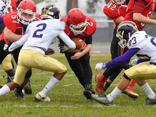 Riverheads' Devin Morris braces himself with the ball as Essex's Avante' Banks and William Clarke go for the tackle during a VHSL Class 1 state semifinal game played in Greenville on Saturday, Dec. 1, 2018.