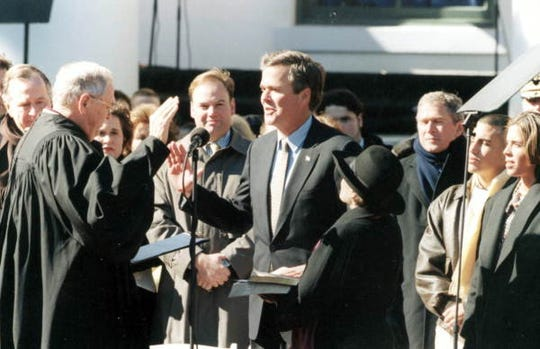 In this January 5, 1999, file photo, Jeb Bush takes the oath of office from Florida Supreme Court Chief Justice Major B. Harding, with wife, Columba at side. (L-R in Background: Former President George H. W. Bush, George P. Bush, George W. Bush, Jeb Bush Jr., Noelle Bush.)