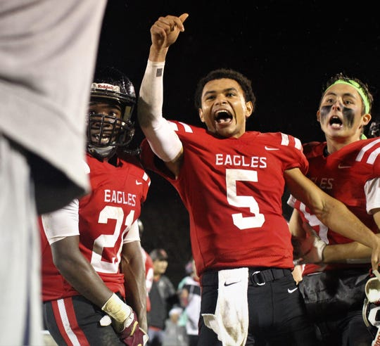 NFC senior quarterback J.D. Jerry (5), senior defensive back Von Hayes (21) and junior linebacker Ryan Jefford celebrate a 23-20 win over Victory Christian in a Class 2A state semifinal.