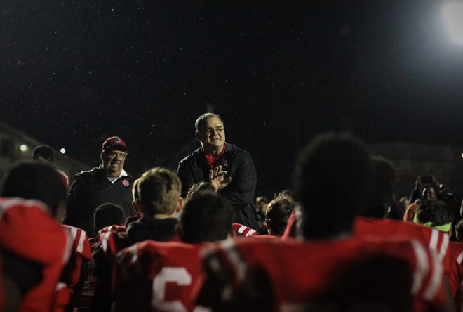 NFC head football coach Steve Price talks to his team under the rain after the Eagles beat Victory Christian 23-20 last Friday night in a Class 2A state semifinal.