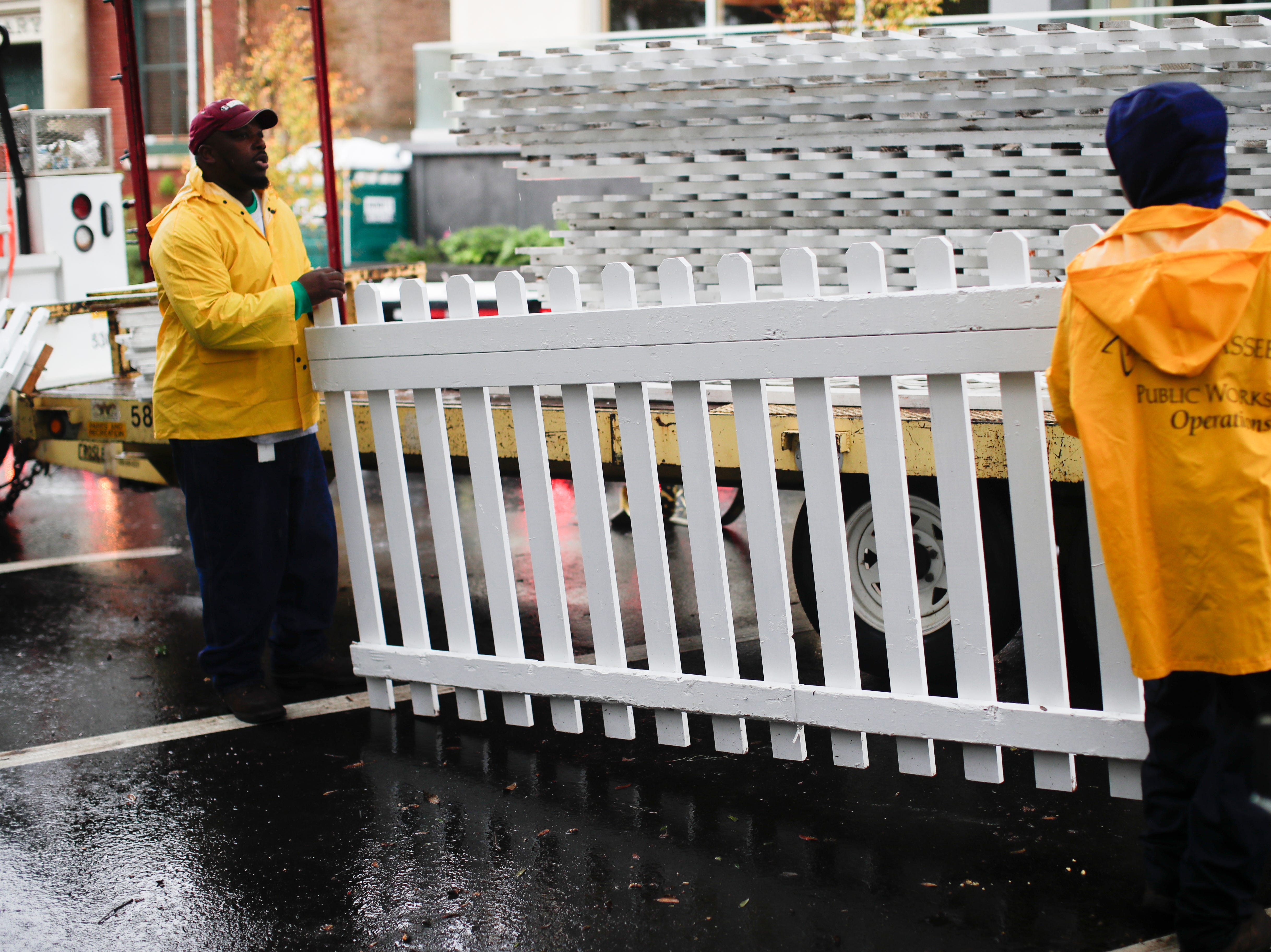 Tallahassee Parks and Recreation workers Gabriel Miles, left and Robert Blake deconstruct fencing put up for Tallahassee Winter Festival after it was canceled Saturday, Dec. 1, 2018.