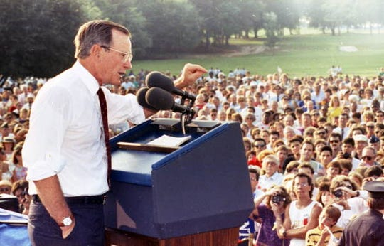 In this Sept. 6, 1990 file photo, former president George H.W. Bush campaigns for the re-election of Congressman Bill Grant.