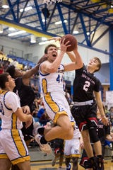 Martin County's Ryan Davis scores the first two points of the game, as South Fork's Gabe Jones defends at right, during the high school boys basketball game Friday, Nov. 30, 2018, at Martin County High School in Stuart.