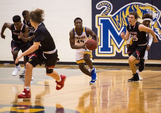 Martin County's George Johnson (center) dribbles downcourt after rebounding the ball against South Fork during the third period of the high school boys basketball game Friday, Nov. 30, 2018, at Martin County High School in Stuart.
