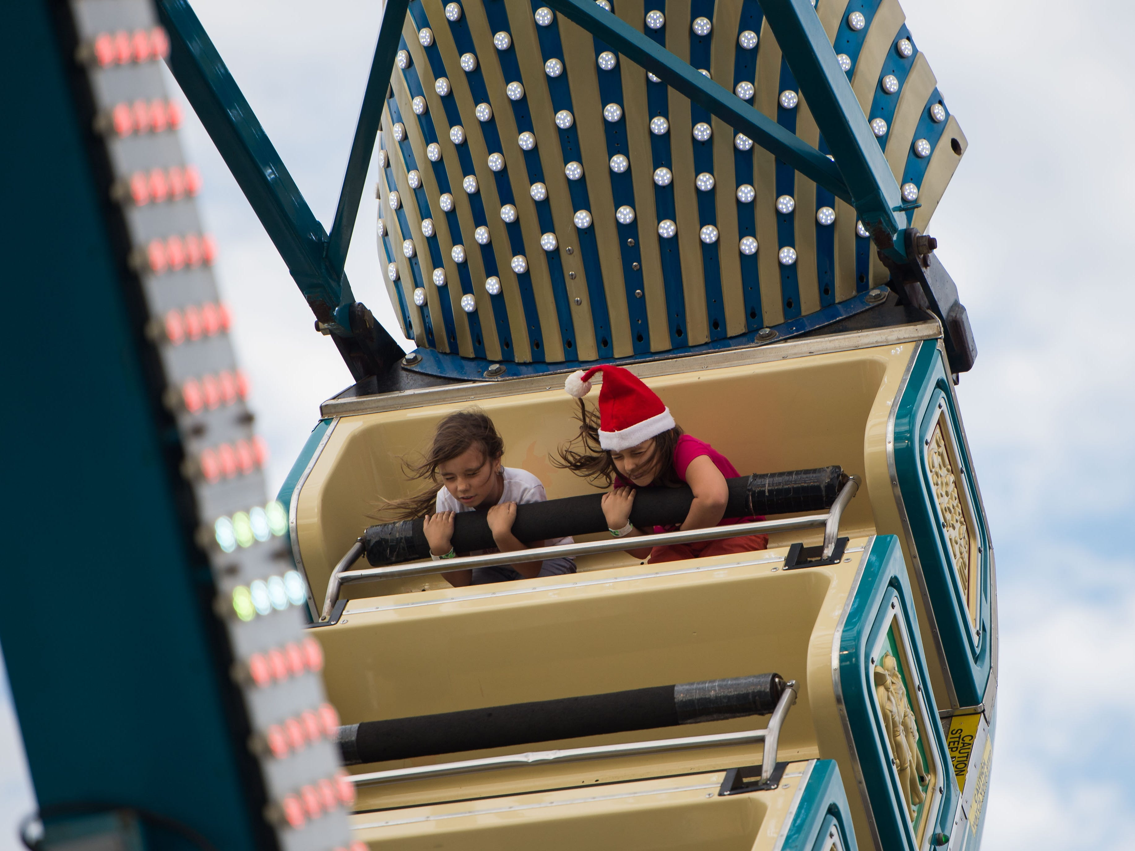 Lexi Mello (right), 7, of Port St. Lucie, shuts her eyes while she and her sister, Kassidy Mello, 9, ride the Pharaoh's Fury at the Port St. Lucie Festival of Lights at the Port St. Lucie Civic Center on Saturday, Dec. 1, 2018, in Port St. Lucie. In addition to rides, food, holiday shopping and live music, the event featured the Snowflakes & Snowmen parade and tree lighting.