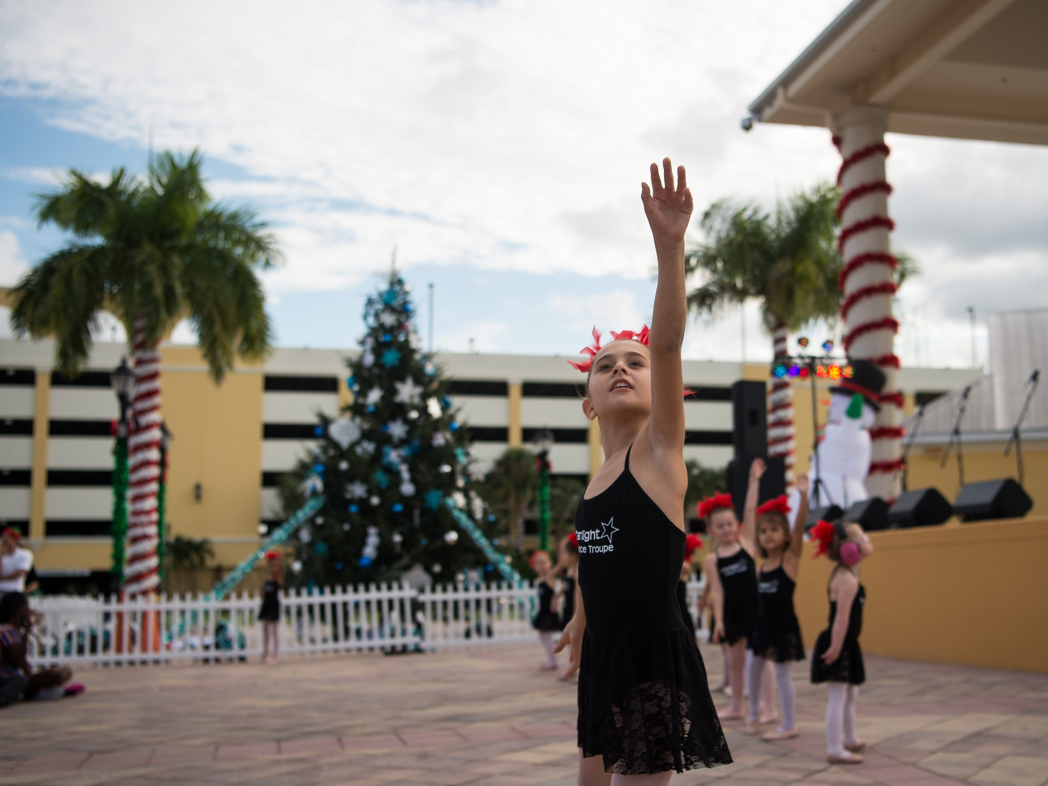 """I help the minis — in case they forget anything, they can just peek over,"" said Starlight Dance Troupe class assistant Hazel Sessanna, 8, of Port St. Lucie, after dancing to a Charlie Brown Christmas song at the Port St. Lucie Festival of Lights on Saturday, Dec. 1, 2018, at the Port St. Lucie Civic Center. ""It's my favorite holiday,"" Hazel said, ""because it's Jesus' birthday...and I like the Christmas trees,"" she added, giggling. In addition to rides, food, holiday shopping and live entertainment, the event featured the Snowflakes & Snowmen parade and tree lighting."