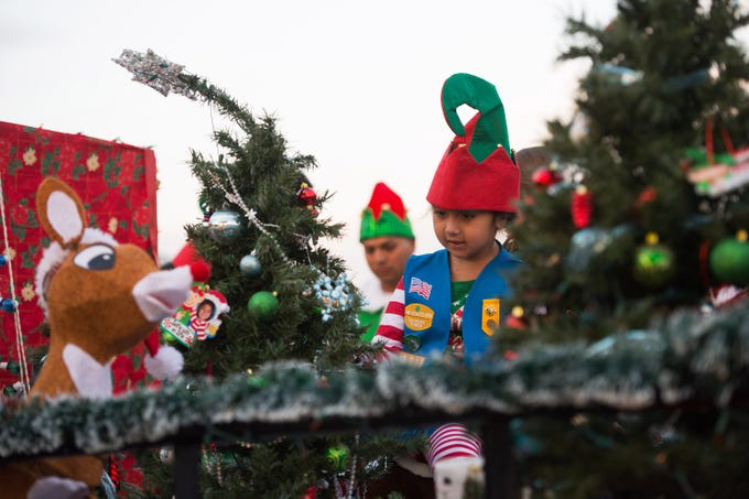 """Girls Scout Troop 51013 member Mia Garcia, 6, of Vero Beach, helps decorate the troops' float before the start of the Sebastian Christmas Parade on Saturday, Dec. 1, 2018, in Sebastian. """"We decorated the float with Christmas trees, presents and reindeer this year,"""" said Garcia adding, """"It is fun."""""""