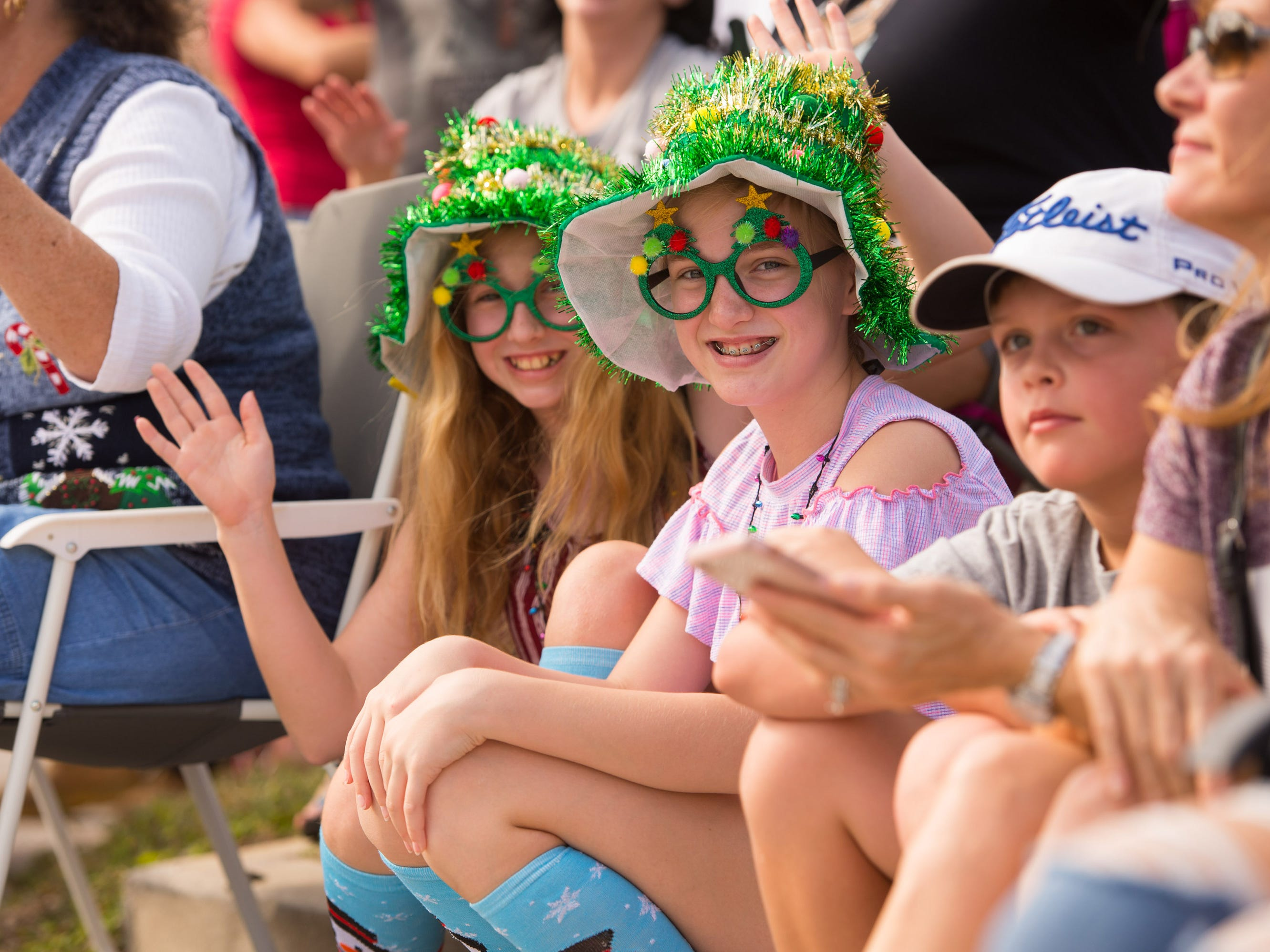 """Ayla Thieme, 12, (left) and her friend Caroline Fisher, 12, both of Stuart, watch the 33rd annual Hobe Sound Christmas Parade on Saturday, Dec. 1, 2018 in Hobe Sound. """"We are having fun,"""" said Thieme adding, """"It's the best time of the year."""" The event included 1,500 parade participants and a craft stroll."""
