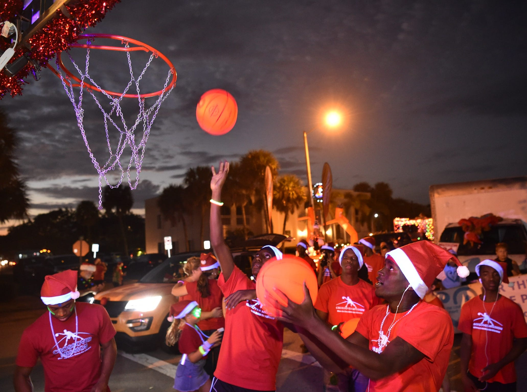 "Evan Chambliss (right), 18, of Vero Beach, with the Crossover Mission float, prepares to walk in the 34th annual Centennial Christmas Parade along Ocean Drive on Saturday, Dec. 1, 2018, in Vero Beach. ""I become a better player in basketball and school academics,"" he said of the organization, which he has been a part of for four years. ""My job tonight is just to amaze the crowd with my dribbling,  and staying focused on my dribble routine."" The fourth annual Candy Cane 3K preceded the parade."