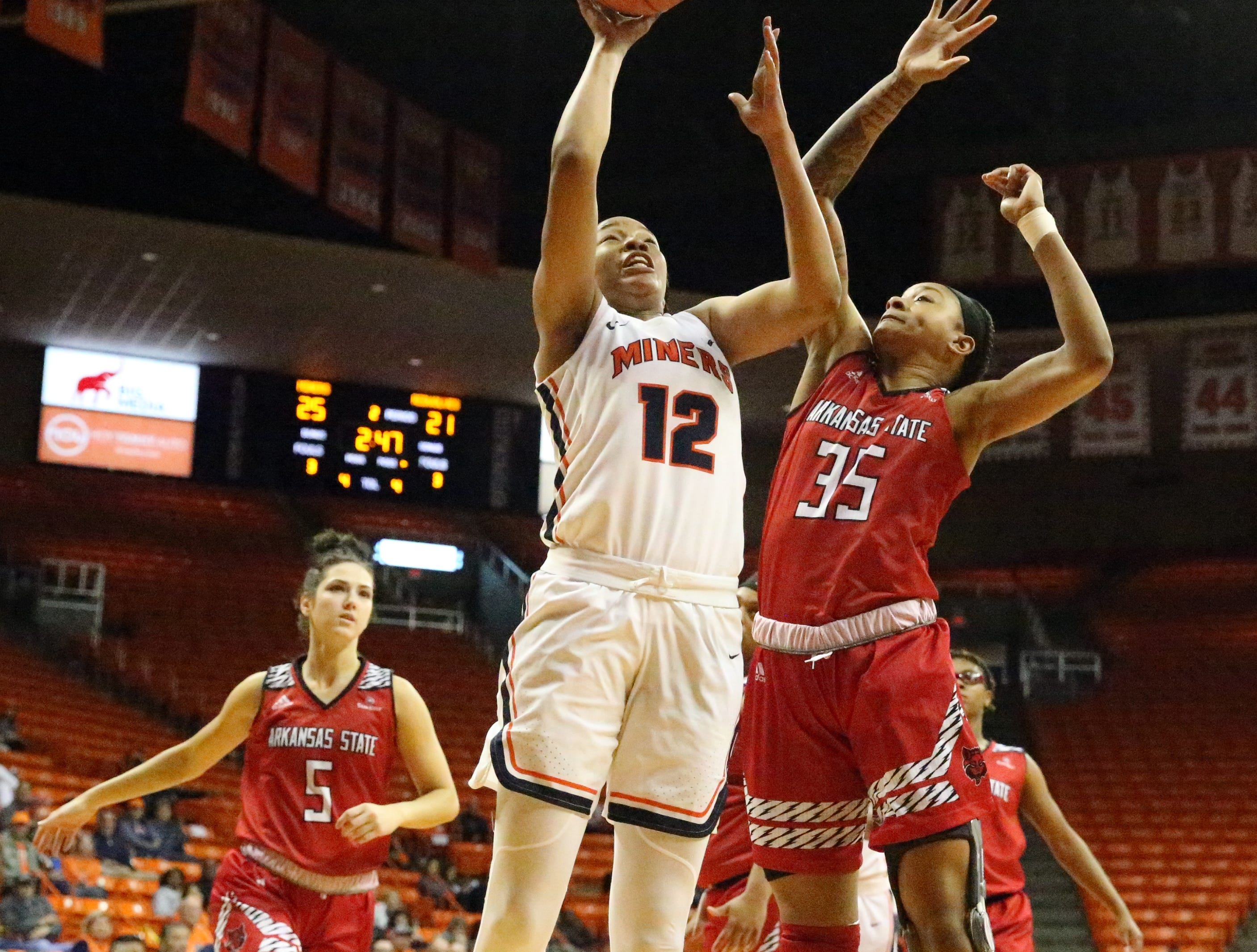 Ariona Gill, 12, of UTEP drives to the basket for two against Peyton Martin, 35, of Arkansas State on Saturday in the Don Haskins Center.