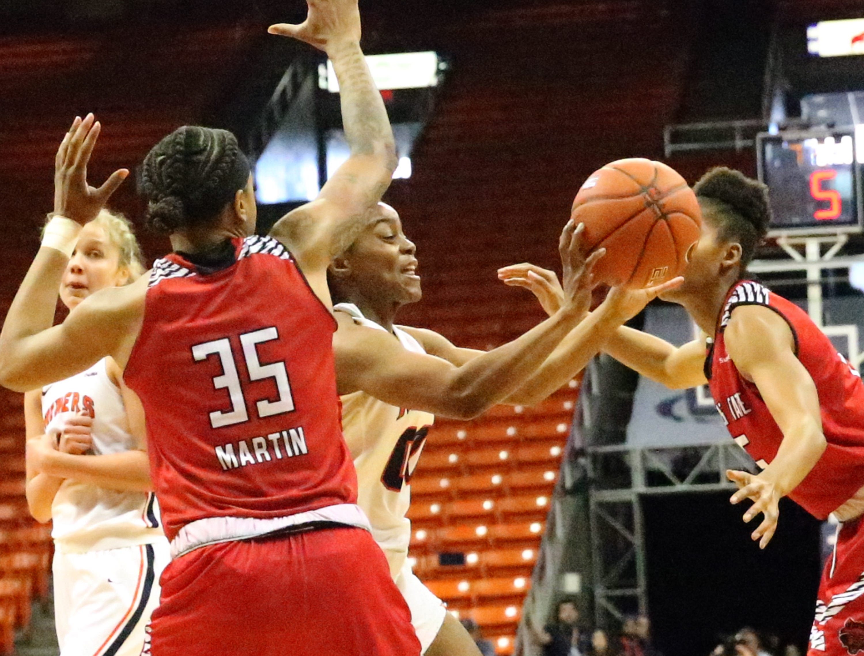 Jordan Jenkins, center, of UTEP finds an outlet while driving to the basket against Arkansas State Saturday in the Don Haskins Center.