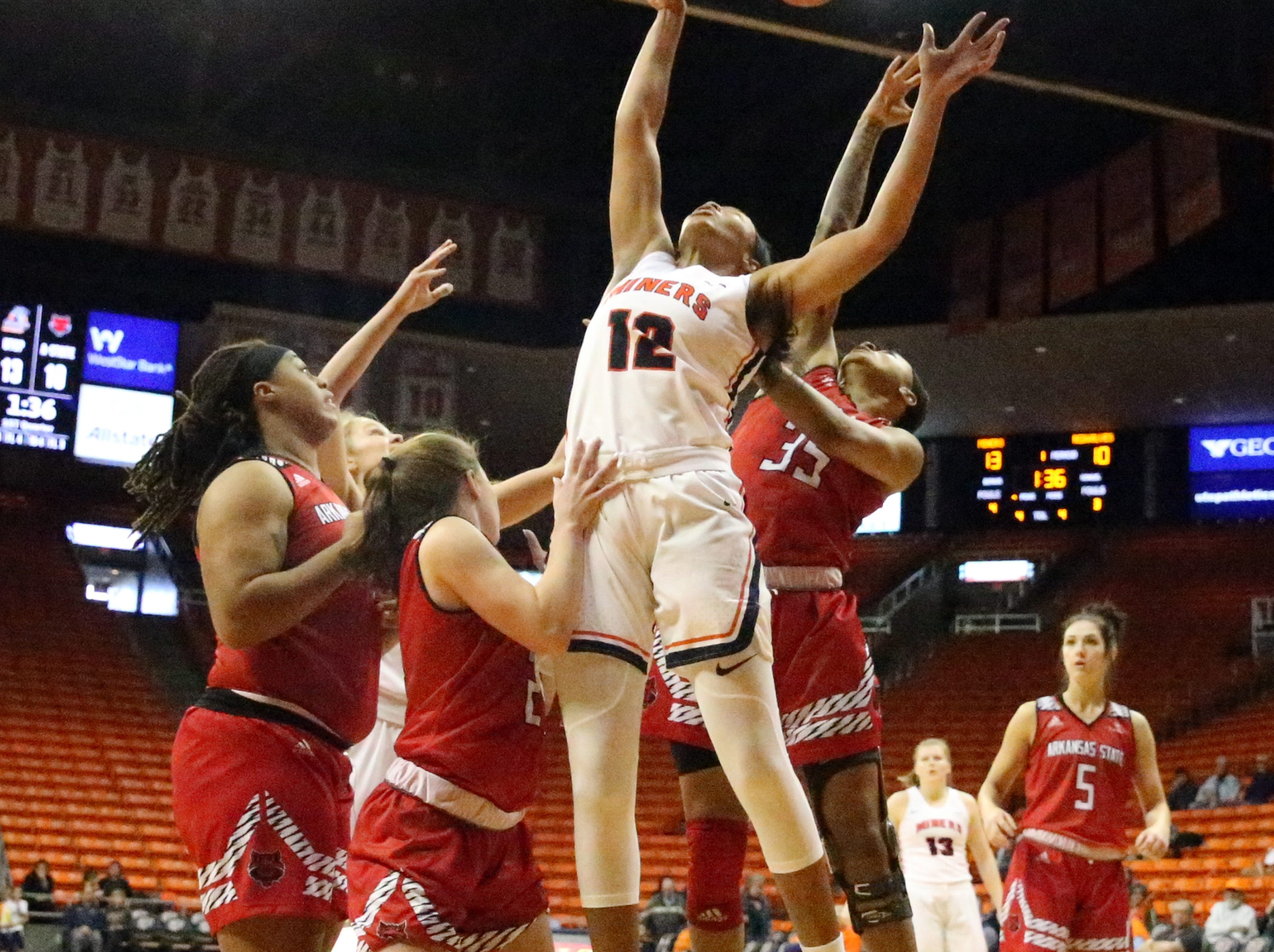 Ariona Gill, 12, of UTEP gets the ball deflected whild driving to the basket against Arkansas State Saturday.