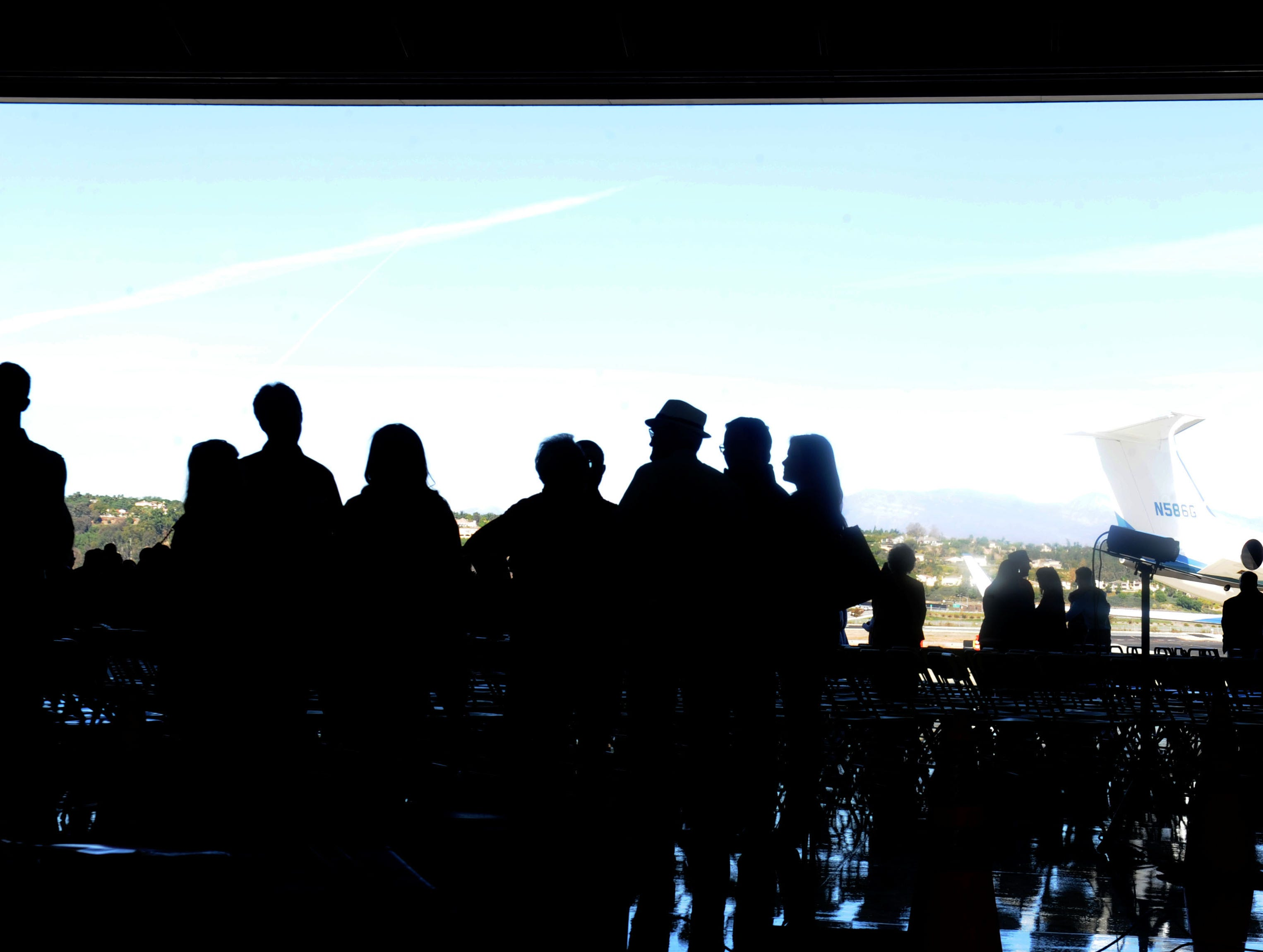 A large group of people gather in a hangar at the Camarillo Airport for a ceremony remembering Todd McNamee, the late Ventura County airports director.