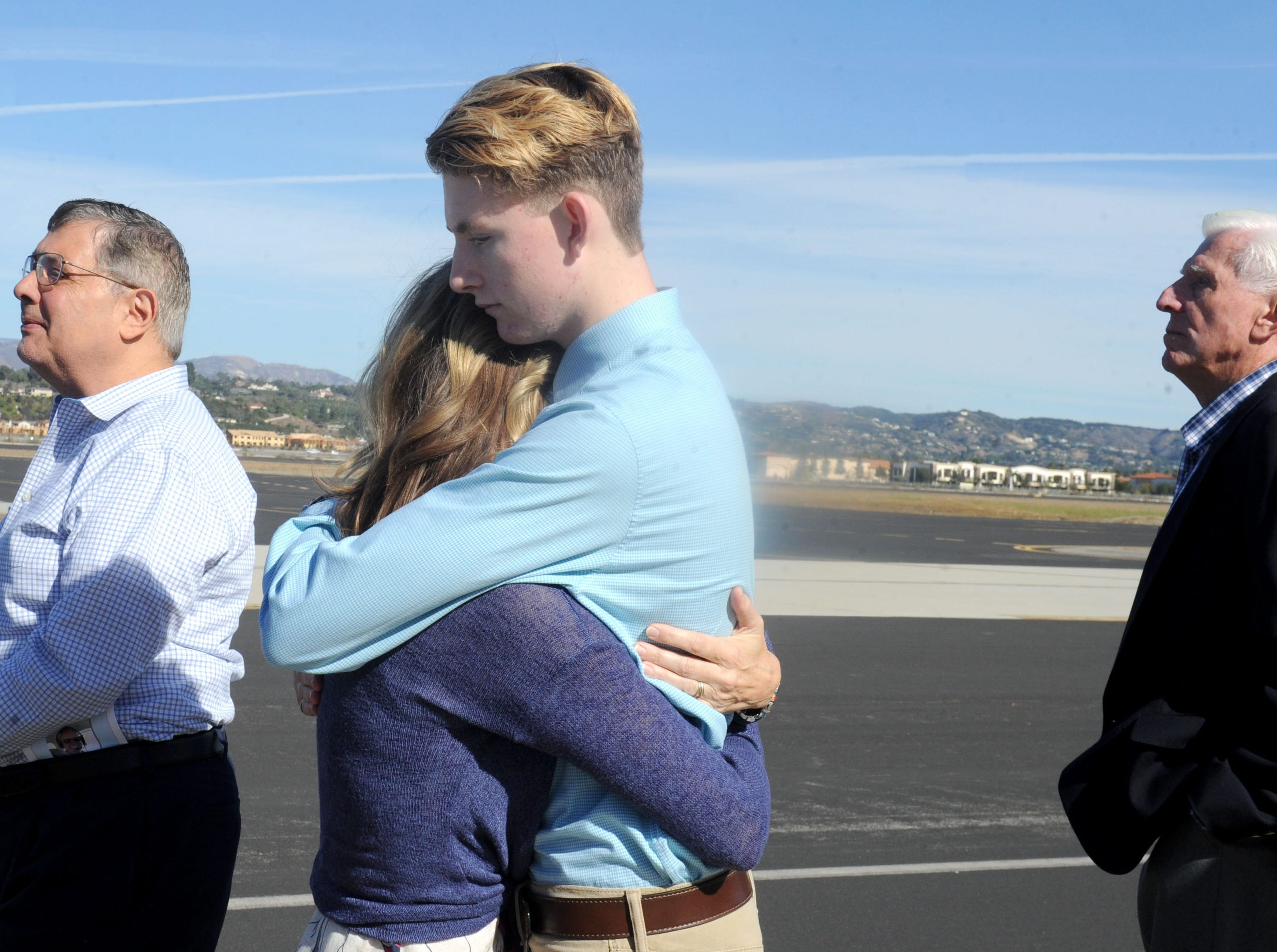 JT McNamee hugs his mother, Ann McNamee, at a memorial service for his father, Todd McNamee, at the Camarillo Airport.