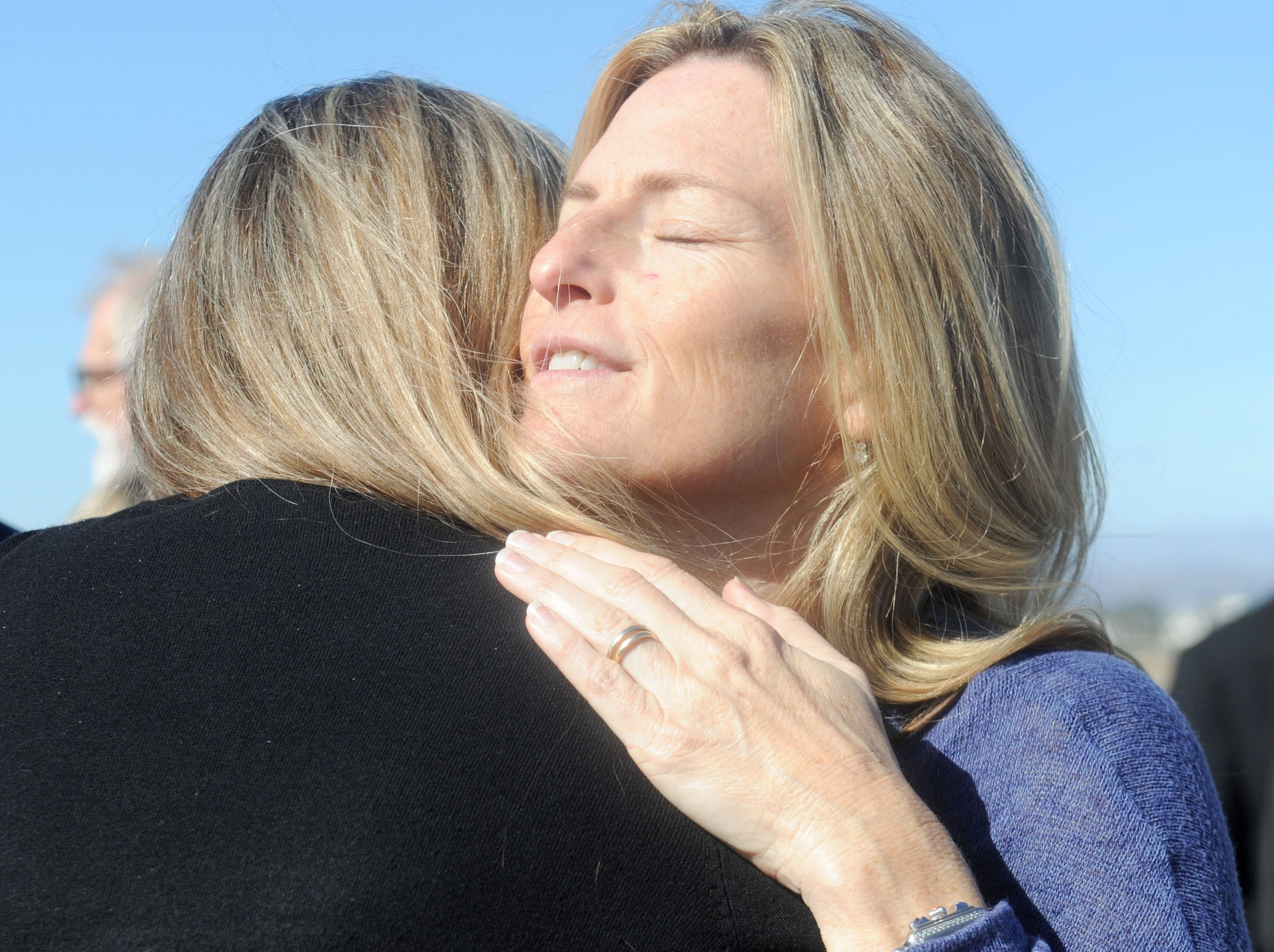 Ann McNamee hugs people at the memorial service for her husband, Todd McNamee, on Saturday at the Camarillo Airport. Todd McNamee was the Ventura County airports director.