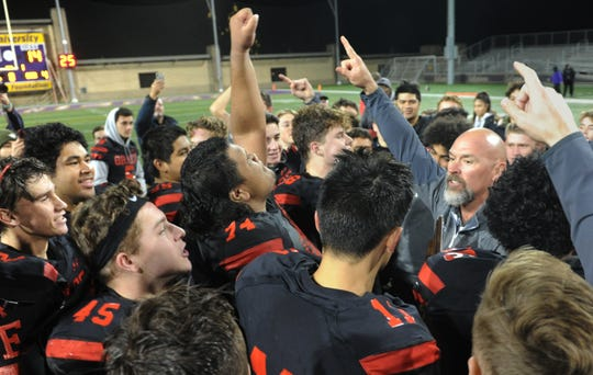 Head coach Josh Henderson, right, celebrates with his players after Grace Brethren defeated St. Augustine 28-14 in the CIF-State Division 2AA SoCal Regional championship Friday night at Cal Lutheran. Grace Brethren will play in the CIF-State Bowl Championship on Dec. 14 at Cerritos College.
