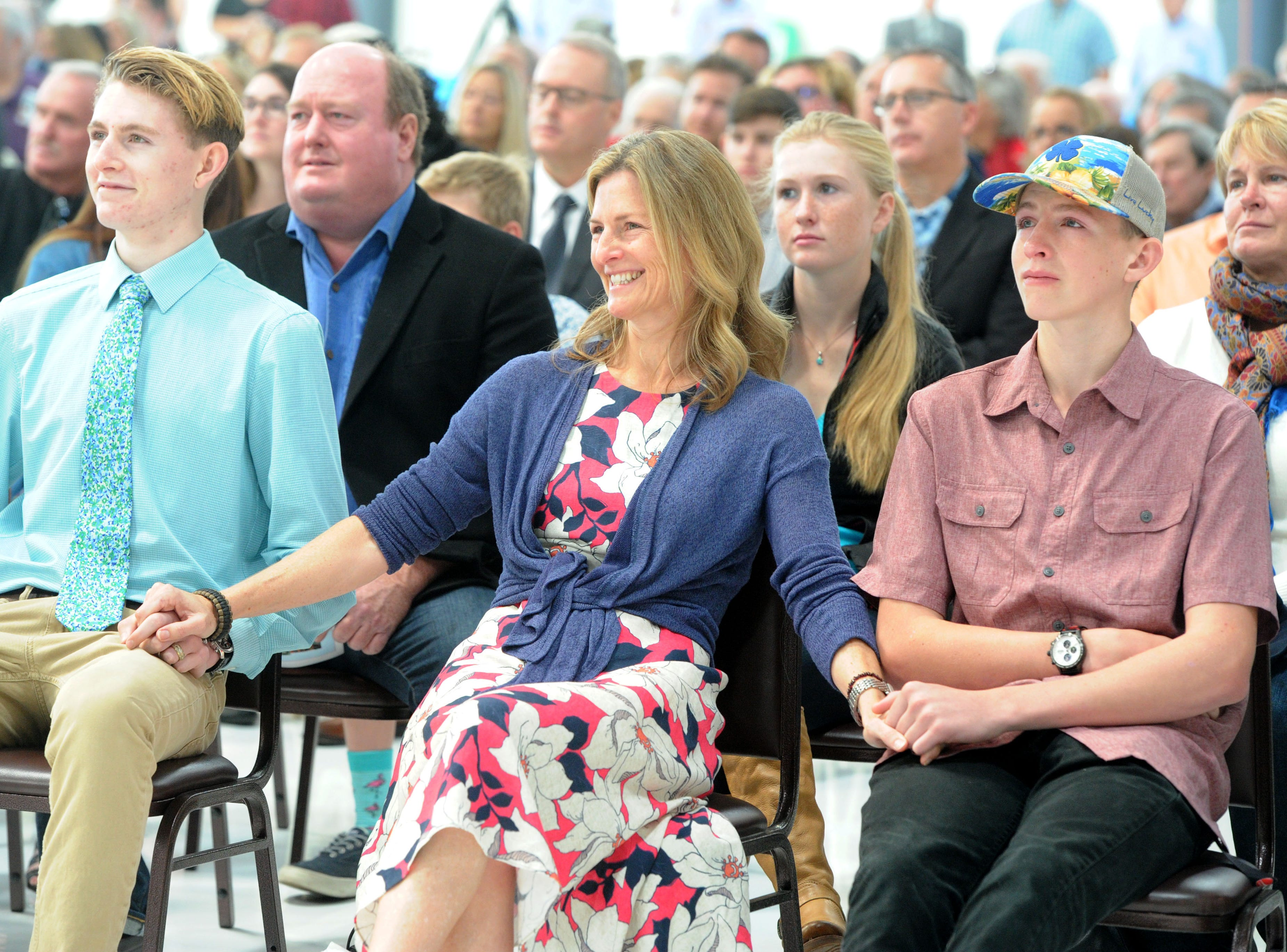 JT McNamee, left, and Peter McNamee hold the hands of their mother, Ann McNamee, at the public memorial service for Todd McNamee on Saturday at the Camarillo Airport. Todd McNamee died in a car crash at the Camarillo Airport last month.