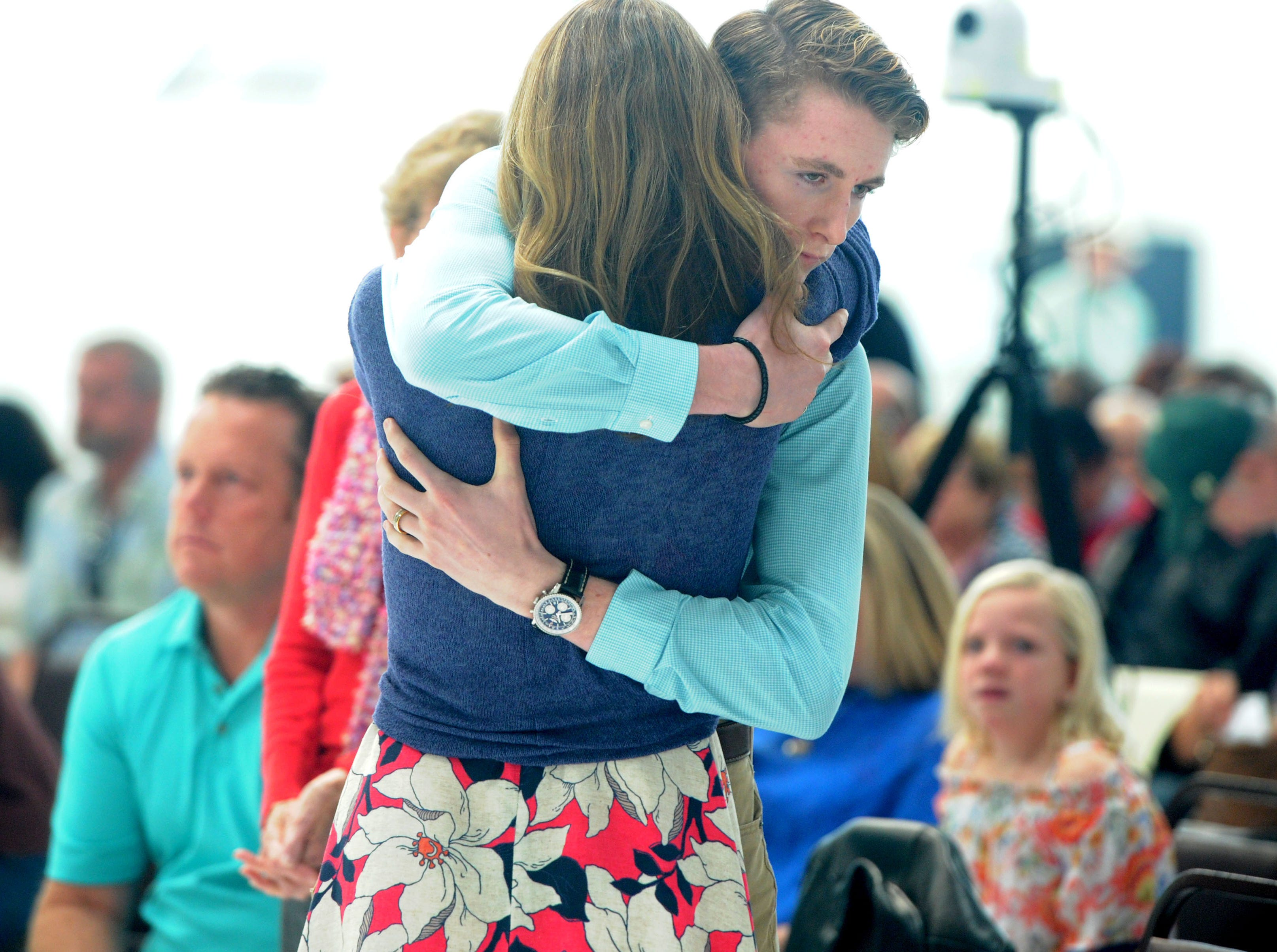 JT McNamee hugs his mother during a ceremony remembering his late father at the Camarillo Airport. Todd McNamee was the Ventura County airports director.