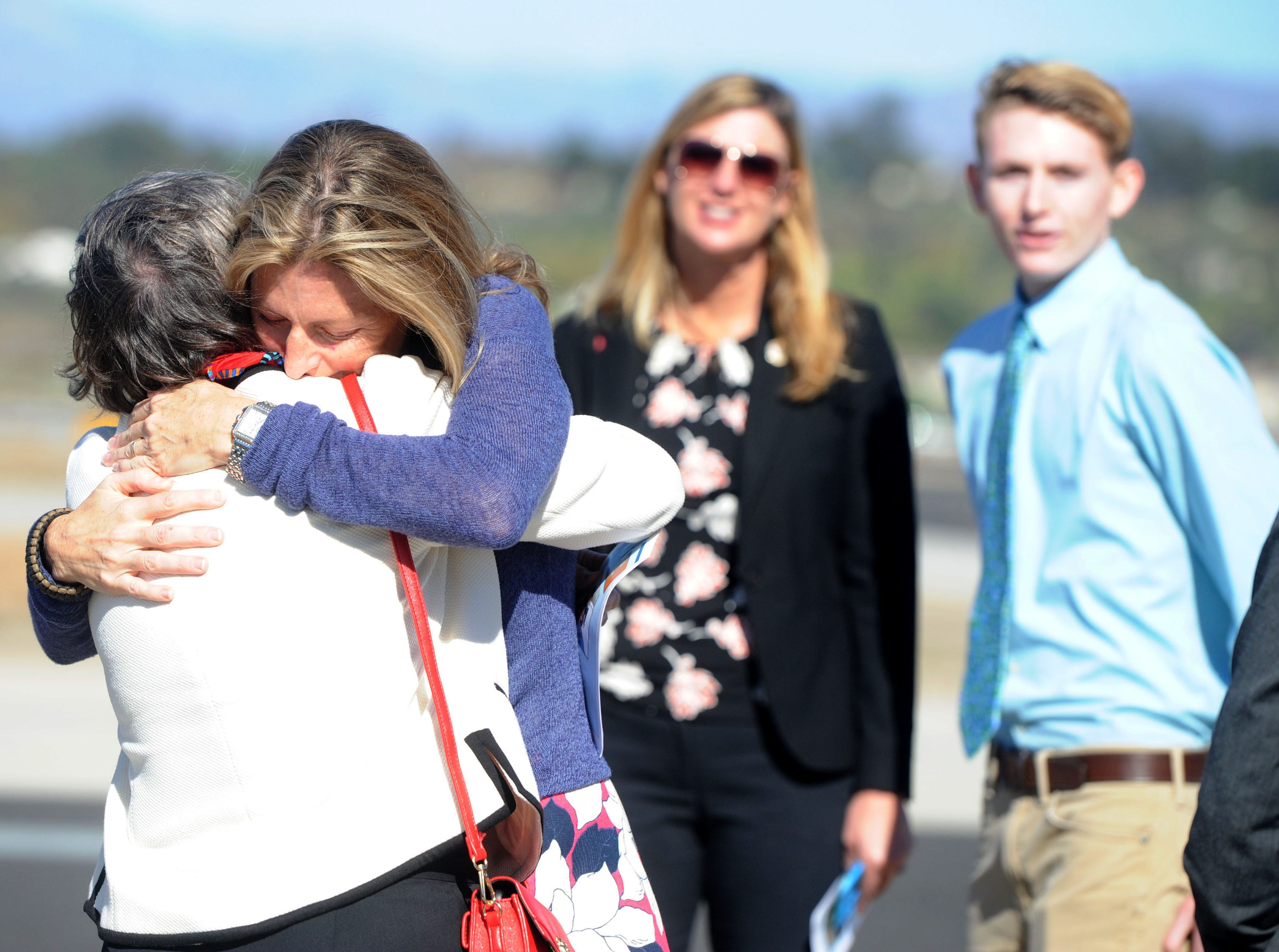 Ann McNamee hugs people at a ceremony remembering her late husband, Todd McNamee, at the Camarillo Airport.