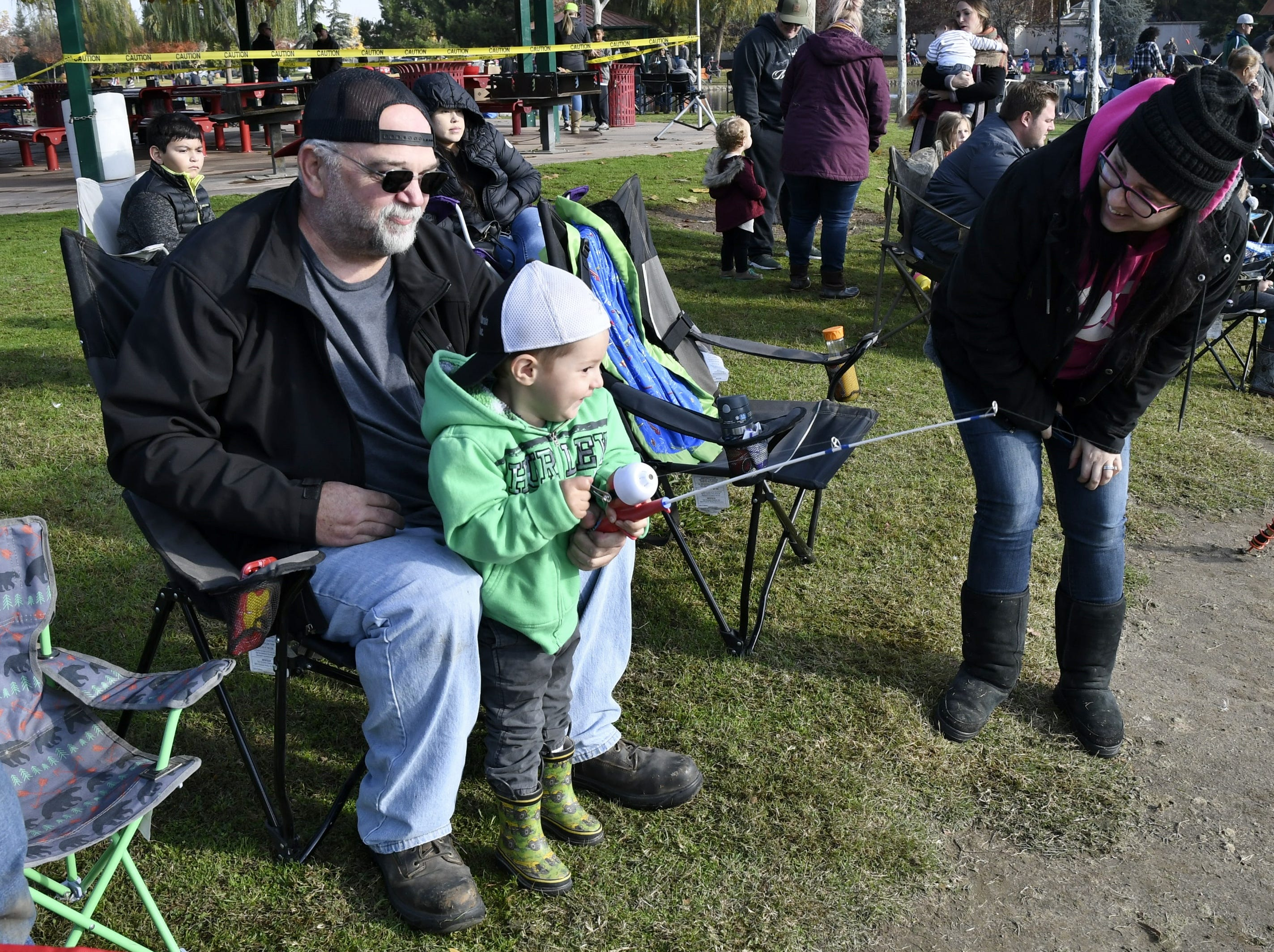 Jerrell Morris watches as grandson Lee Uzzell, 2, reels in his line at the annual Tulare Parks and Recreation Trout Fishing Derby at Del Lago Park on Saturday, December 1, 2018.