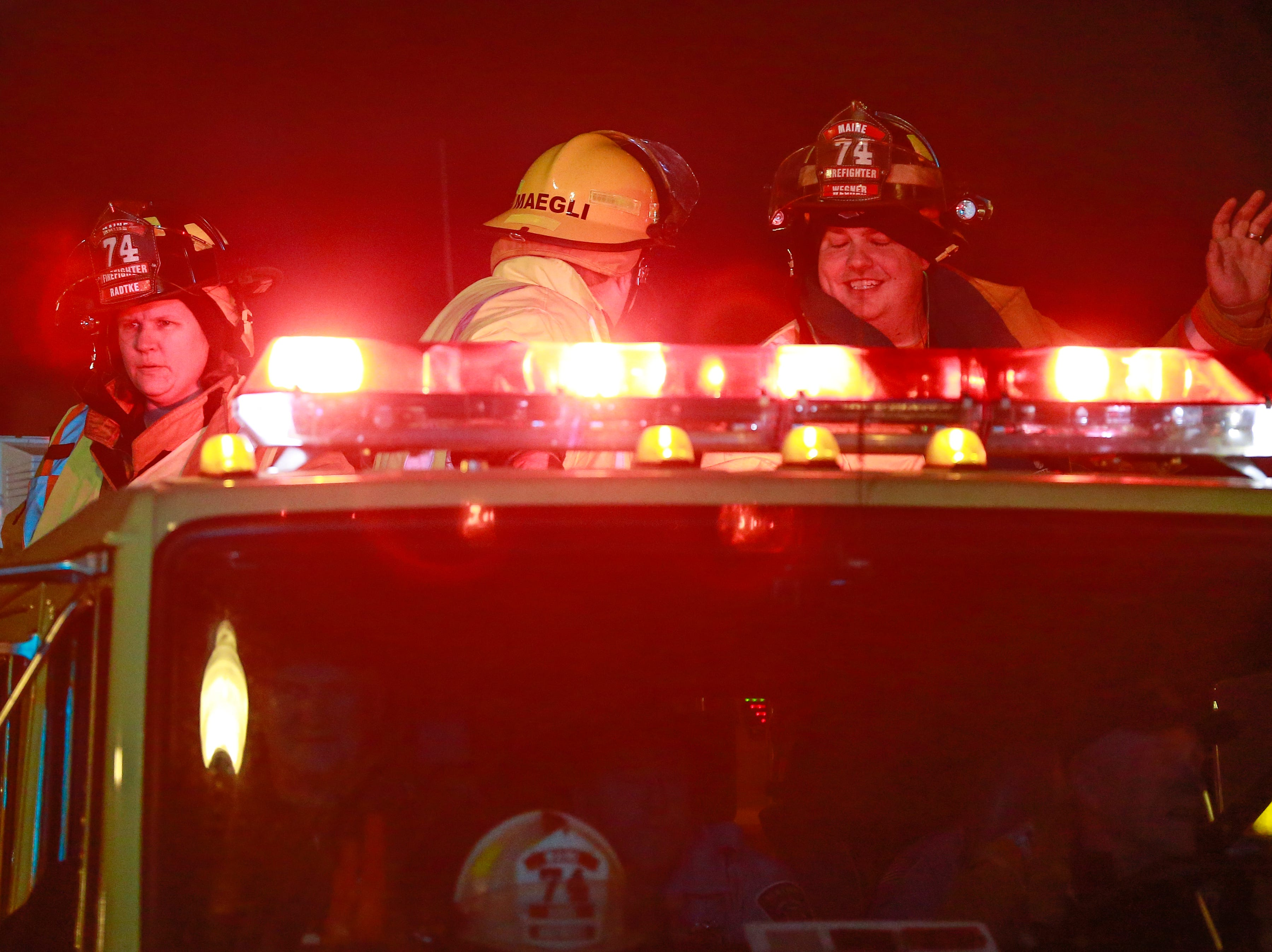 Firefighters wave at people during the Wausau Holiday Parade Friday night on Stewart Avenue in Wausau, Wisc. T'xer Zhon Kha/USA TODAY NETWORK-Wisconsin