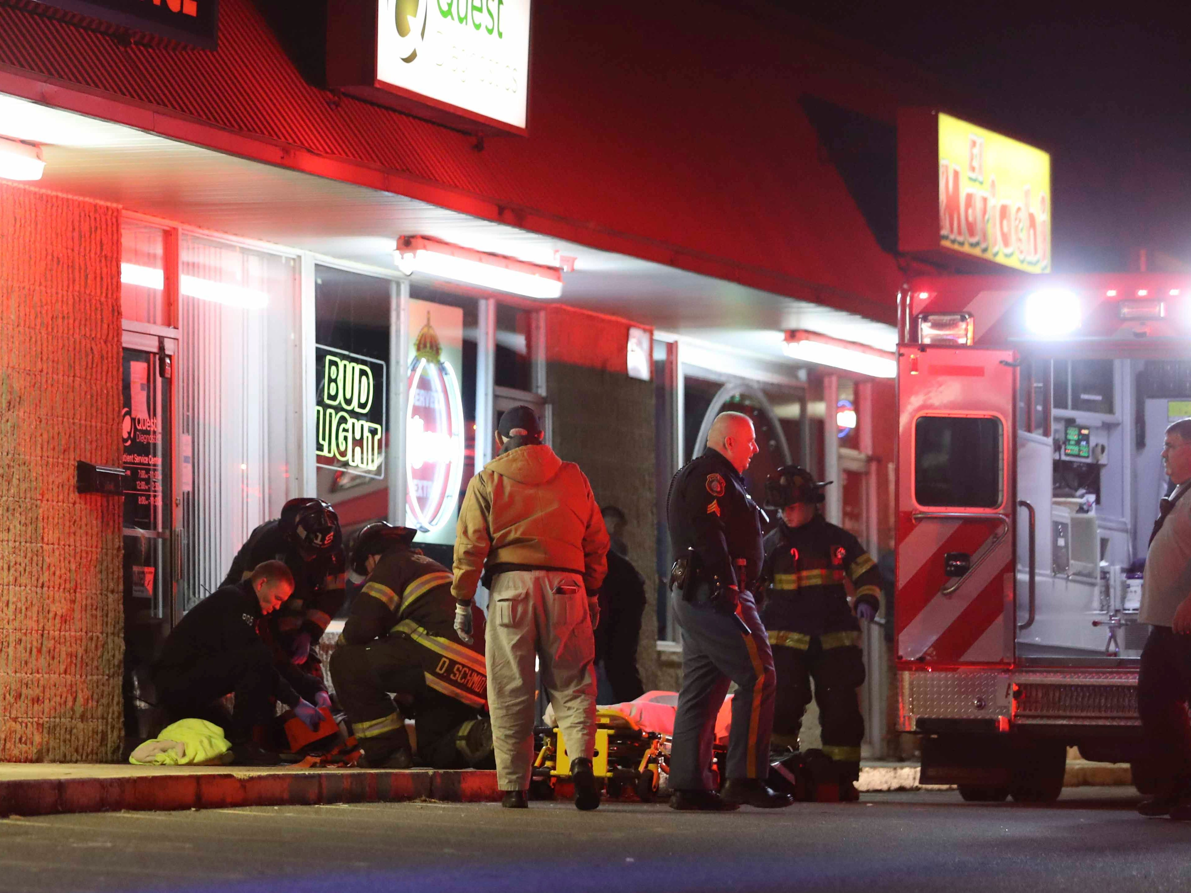 Emergency personnel tend to woman struck and pinned against a storefront wall outside Casa Mariachi restaurant and bar on East Basin Road about 11:10 p.m. Friday.