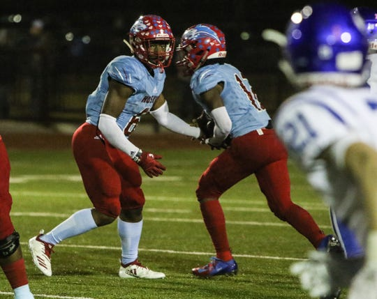 Hirschi's Daimarqua Foster hands the ball to Stavonte Vaughn in a playoff game last season. Vaughn is taking over the starting running back role in place of Foster for the Huskies this season.