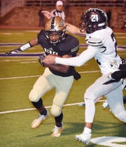 Rider's Nick Darcus (2) is hit by Canyon Randall defensive back Taymarion Johnson (21) during third quarter action Friday night in Childress for the 5A Division II regional Semifinal. Rider defeated Canyon Randall, 38-7.