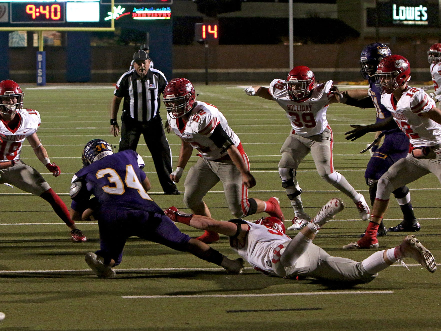 Holliday's Tanner Bayard (55) hangs on to the jersey of Buffalo's Hector Dominguez (34) for a tackle as several Eagle defenders close in on him Friday, Nov. 30, 2018, in the Region II-3A Div. II regional game at Birdville ISD Athletics Complex in North Richland Hills.